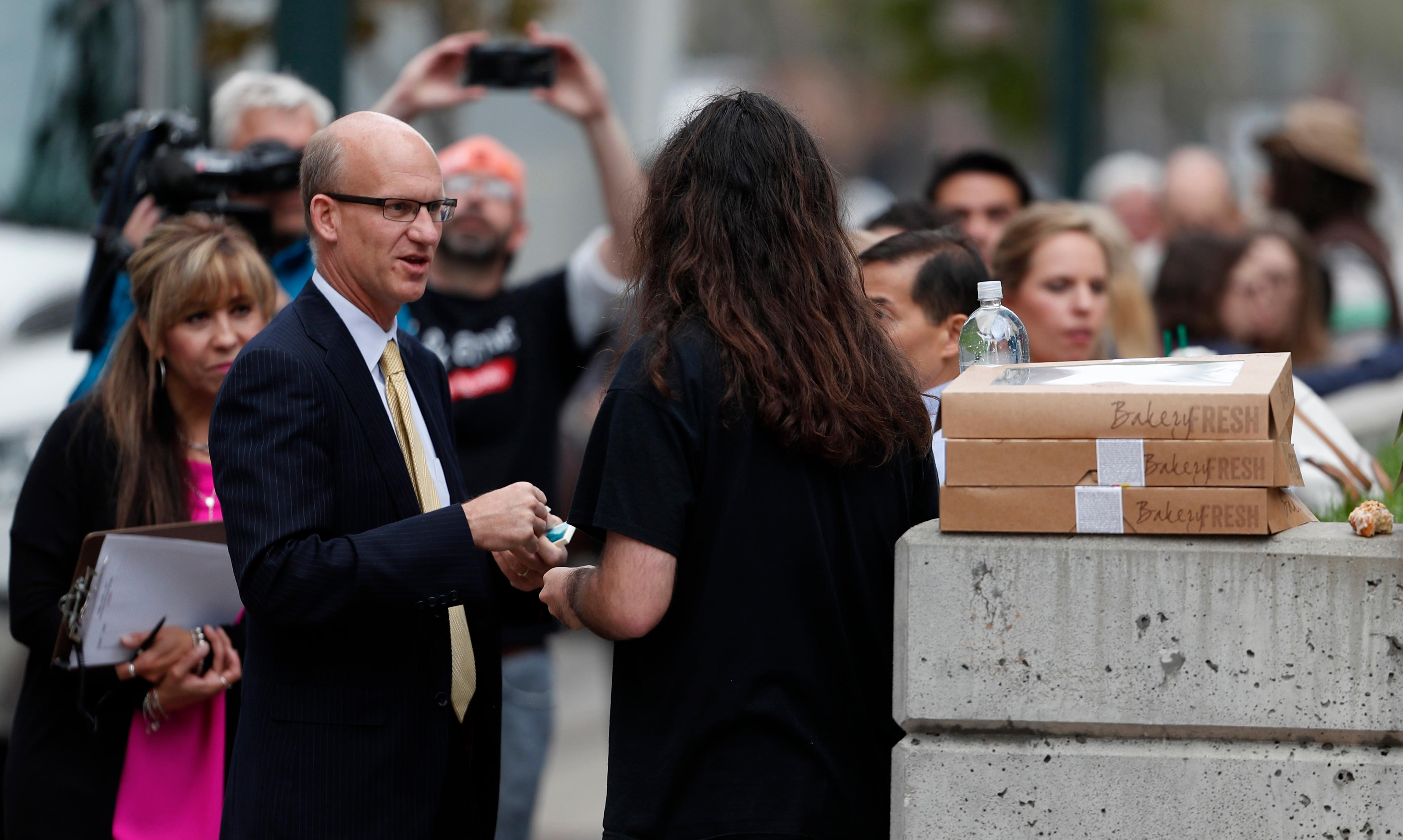 A court officer hands out passes to the public for the morning session in the civil trial for pop singer Taylor Swift, Friday, Aug. 11, 2017, in Denver. Radio station DJ David Mueller sued Swift after her team reported she was groped by Mueller,  to his bosses at a country music station. He is seeking up to $3 million, saying the allegation cost him his job and reputation. Swift countersued Mueller, claiming sexual assault. She is seeking a symbolic $1.   (AP Photo/David Zalubowski)
