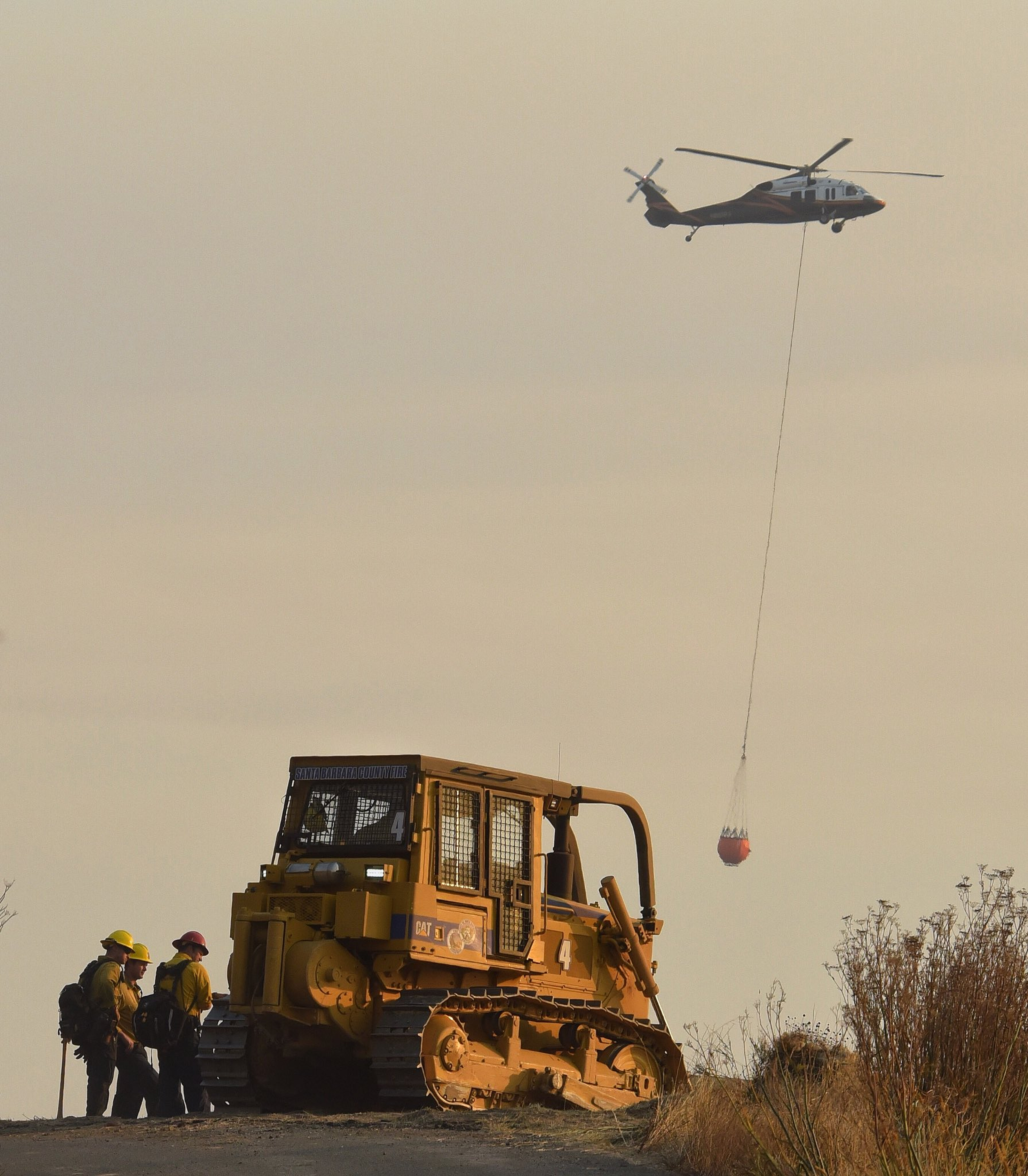 In this photo provided by the Santa Barbara County Fire Department, firefighters and a bulldozer from Santa Barbara County Fire watch from El Camino Cielo as a helicopter readies to make a water drop on a hot spot above Montecito, Calif., Sunday morning, Dec. 17, 2017. (Mike Eliason/Santa Barbara County Fire Department via AP)