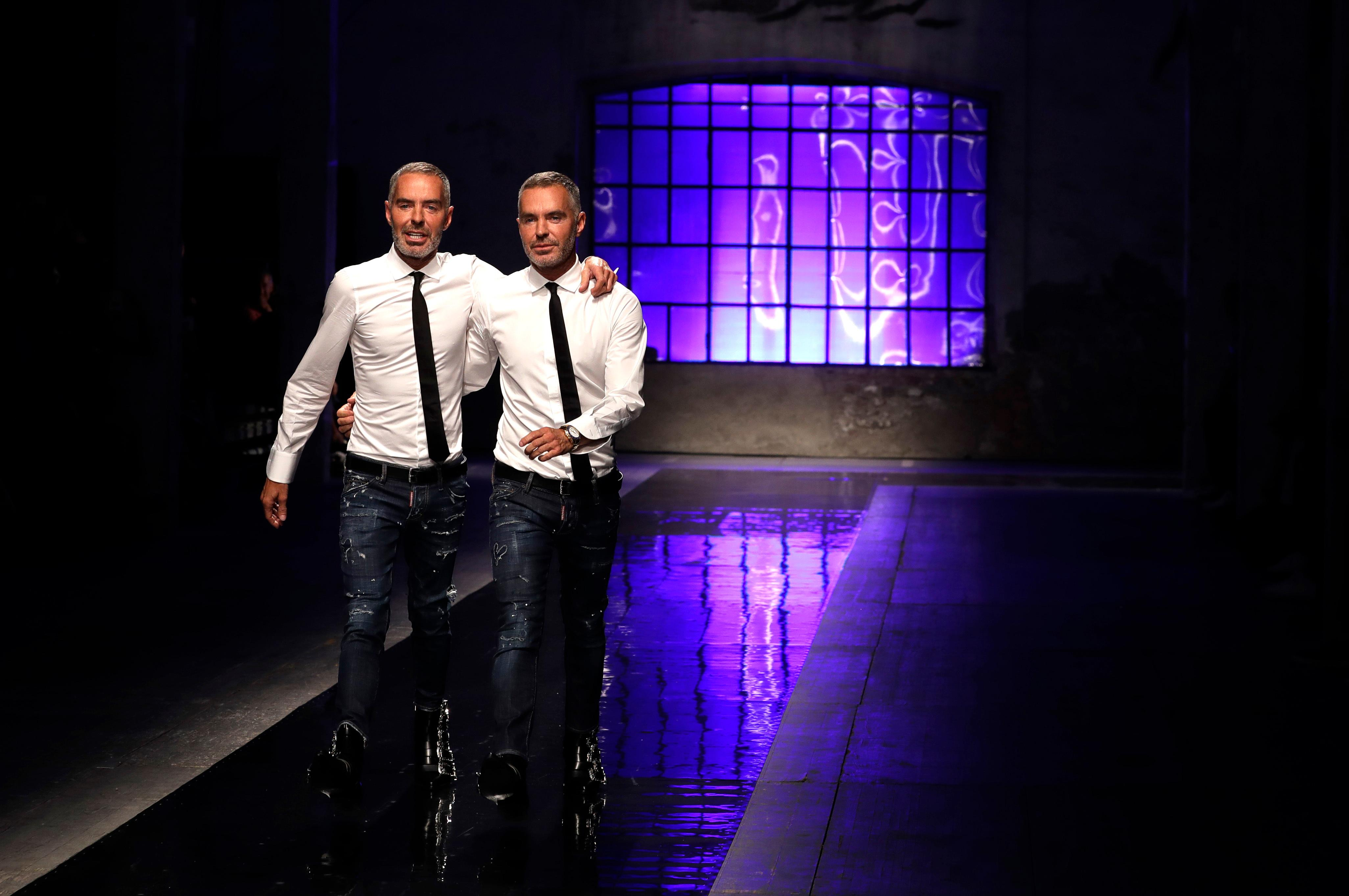 Canadian fashion designers Dean Caten, right, and Dan Caten acknowledge the applause of the audience after presenting their DSquared2 men's Spring-Summer 2018 collection, presented in Milan, Italy, Sunday, June 18, 2017. (AP Photo/Antonio Calanni)