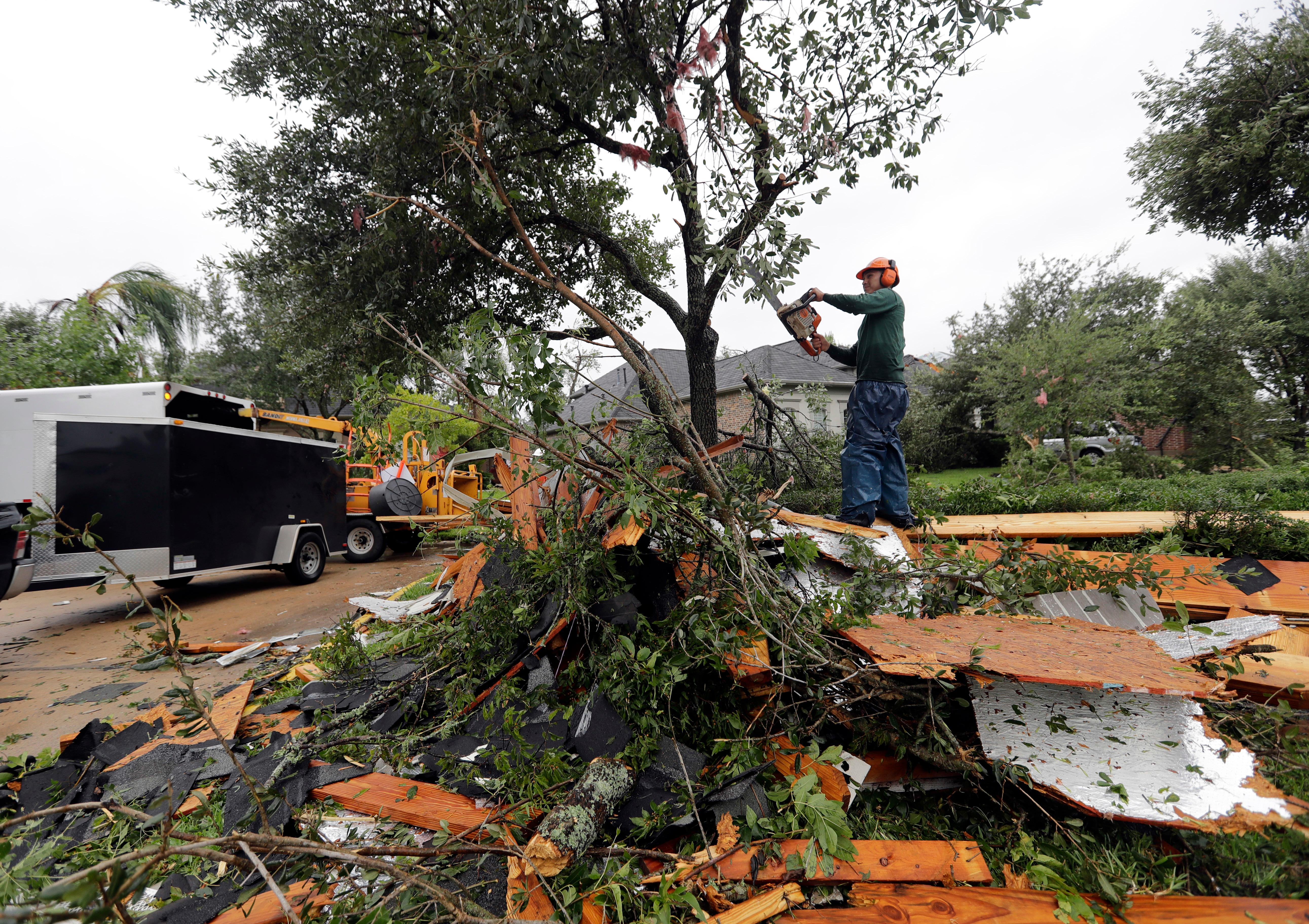 Henry Isaac cuts down broken tree limbs after  Hurricane Harvey Saturday, Aug. 26, 2017, in Missouri City, Texas.  Harvey rolled over the Texas Gulf Coast on Saturday, smashing homes and businesses and lashing the shore with wind and rain so intense that drivers were forced off the road because they could not see in front of them.  (AP Photo/David J. Phillip)