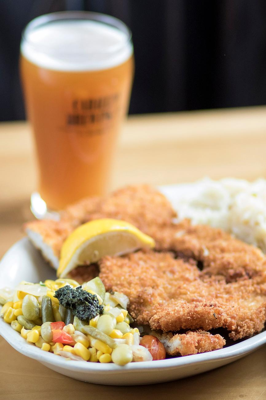 Most of the menu items are inspired by the early Daytonians. Shown here is the Pork Schnitzel with seasonal succotash and braised sauerkraut and Ginger Pale Ale. / Image: Allison McAdams // Published: 1.16.18