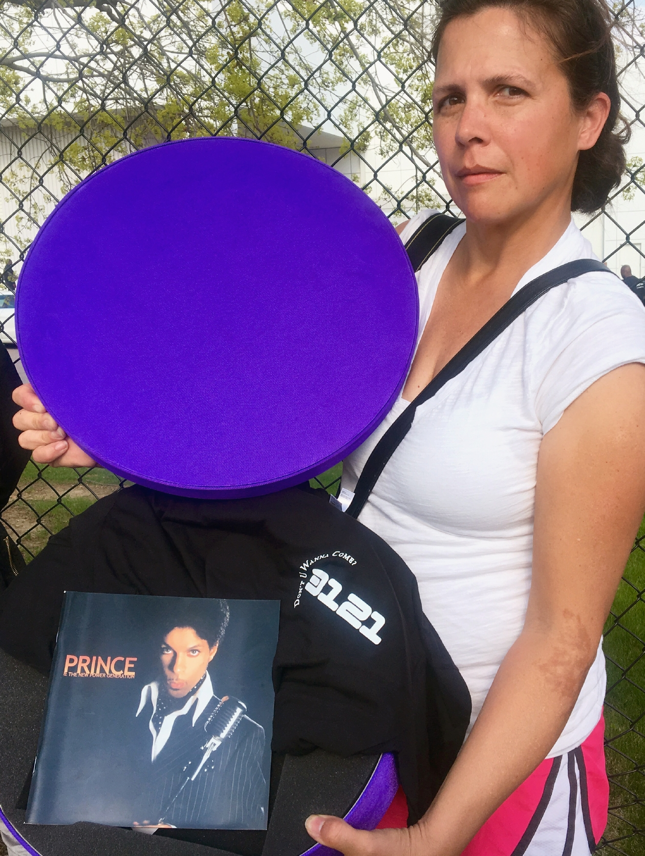 "Colleen Hedtcke, of Hudson, Wis., poses for a photo outside Prince's Paisley Park Studios with a purple hatbox she received containing a Prince booklet and a black T-shirt with ""3121"" printed on it in white- the numbers referring to a Prince album title, in Chanhassen, Minn., Saturday, April 23, 2016. The music superstar was pronounced dead at his Paisley Park estate near Minneapolis on Thursday. He was 57. Round purple boxes were handed out to some fans that were gathered outside the estate. (AP Photo/Jeff Baenen)"