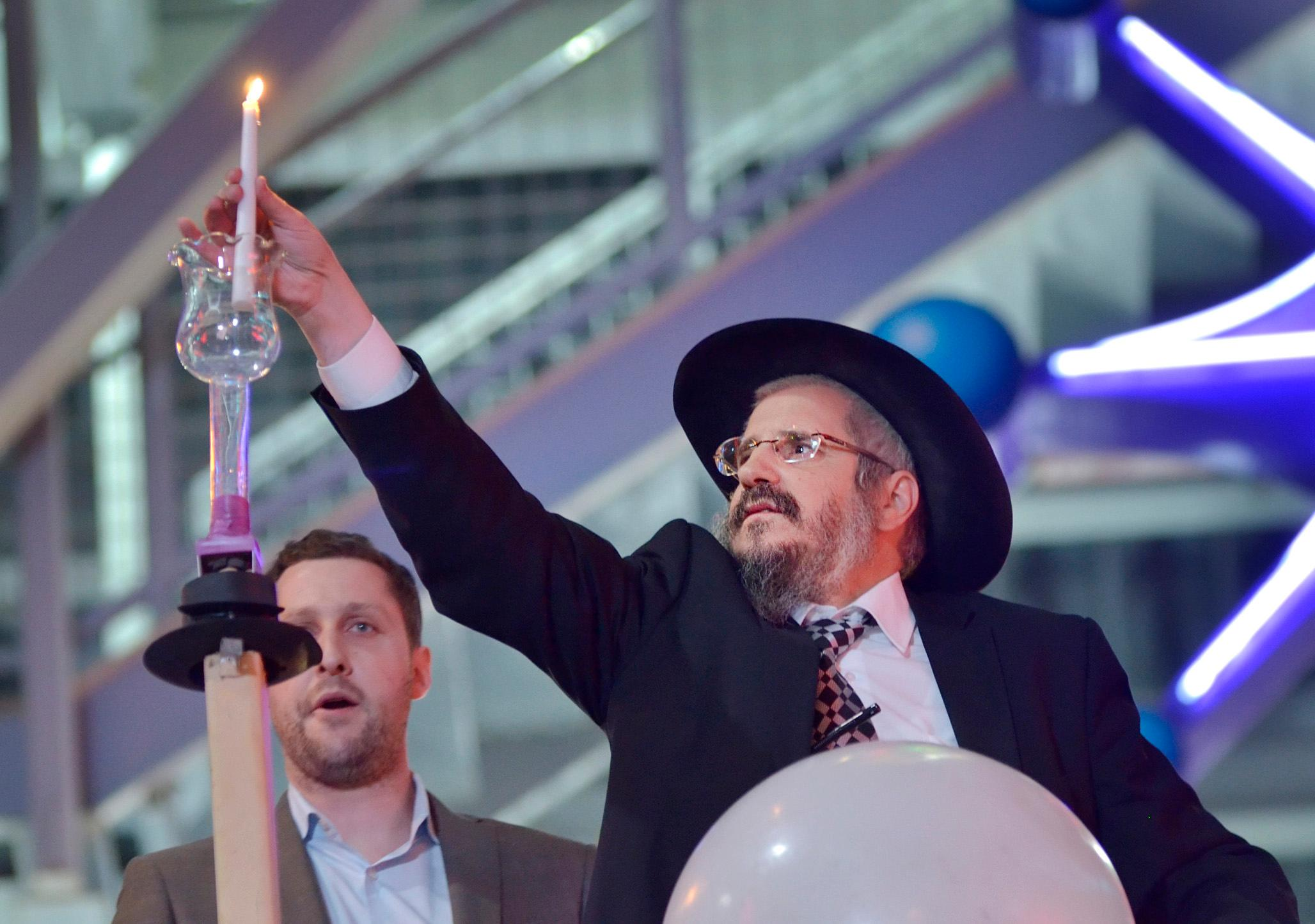 Rabbi Shea Harlig, of the Chabad Jewish Center of Southern Nevada, right, puts a candle into a menorah as Jonathan Jossel, CEO of the Plaza hotel-casino, looks on. Las Vegas Mayor Carolyn Goodman and Patrick Hughes, President and CEO of Fremont Street Experience, were also on hand for the first night of Hanukkah which was marked with the lighting of a 20-foot Grand Menorah on Fremont Street in downtown Las Vegas on Tuesday, Dec. 12, 2017. CREDIT: Bill Hughes/Las Vegas News Bureau