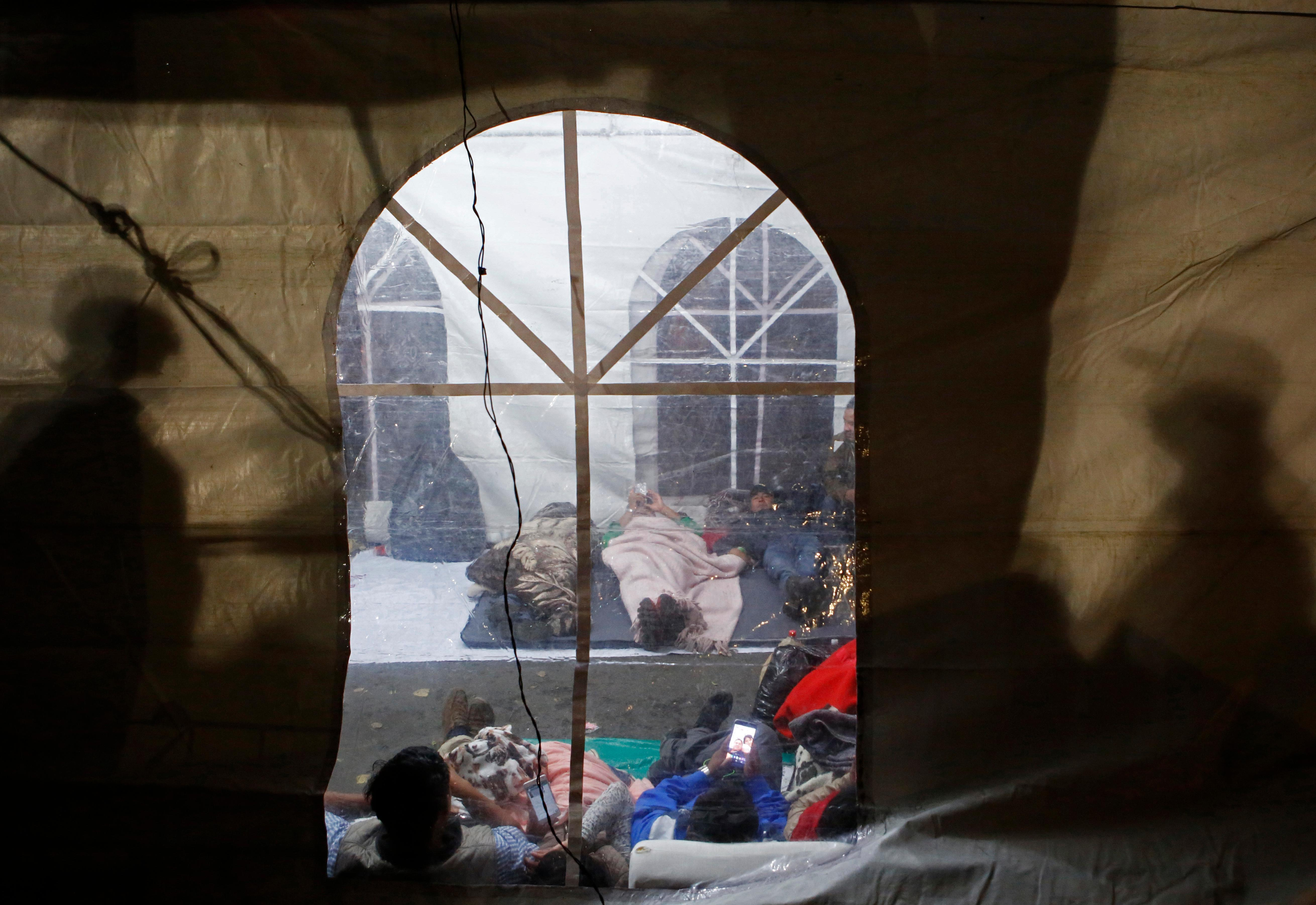 Exhausted family members of people believed to be buried inside a collapsed office building nap in a tent as rescuers continue trying to reach survivors, in the Roma Norte neighborhood of Mexico City, shortly after midnight Saturday Sept. 23, 2017.(AP Photo/Rebecca Blackwell)
