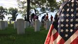 Little Rock students place flags on soldiers' graves