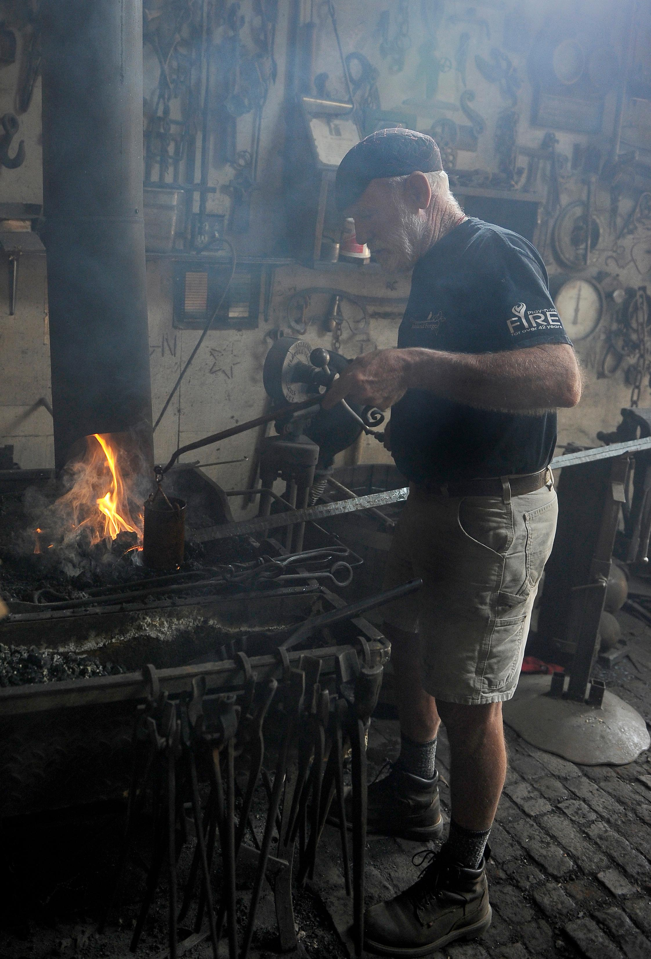 Andy Atkinson / Mail Tribune<br>Ashland Forge owner and operator Dennis DeBey controls his fire while creating a gate for a local resident.
