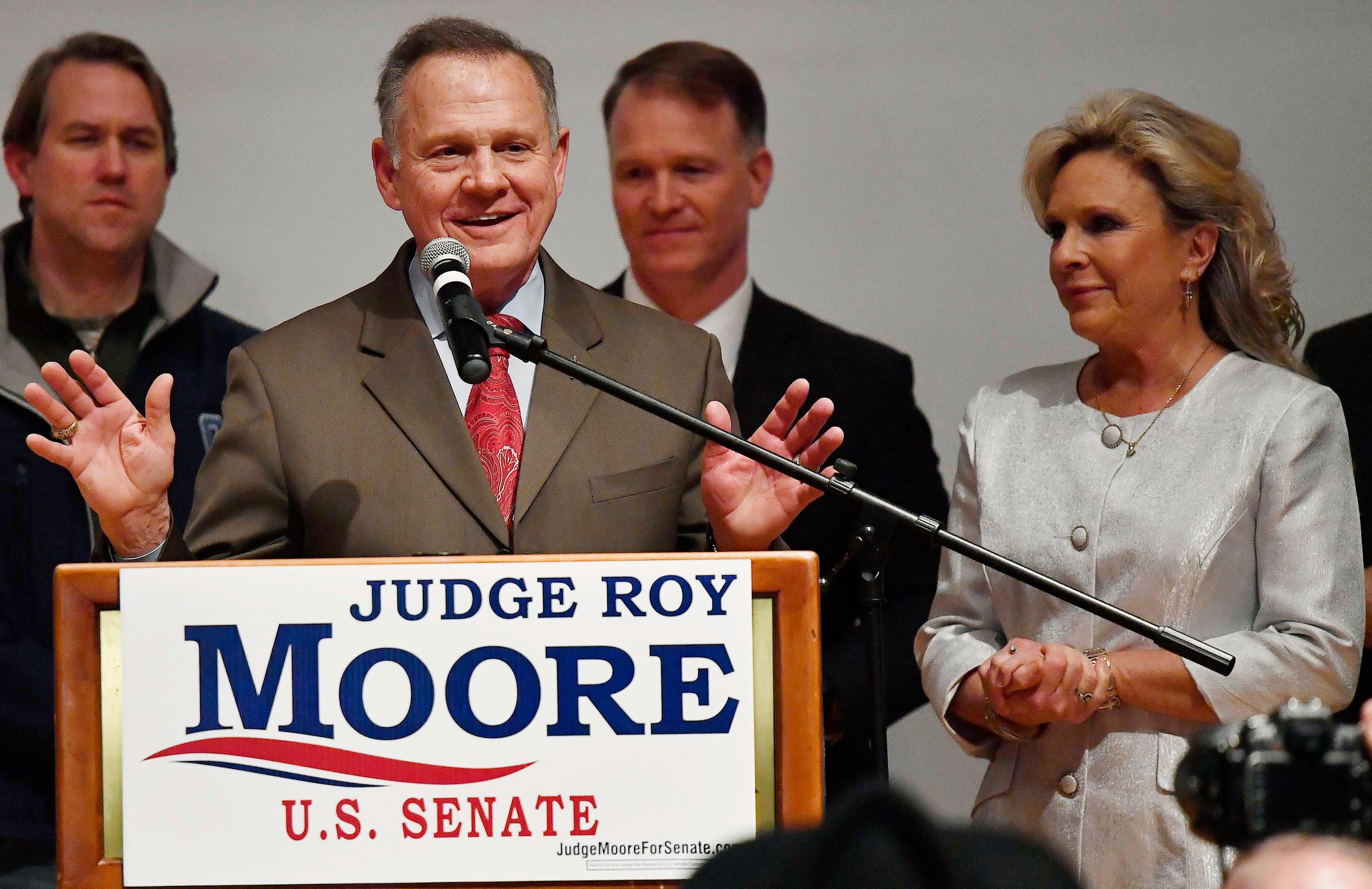 U.S. Senate candidate Roy Moore speaks as his wife Kayla Moore, right, listens at the RSA activity center, Tuesday, Dec. 12, 2017, in Montgomery, Ala. (AP Photo/Mike Stewart)