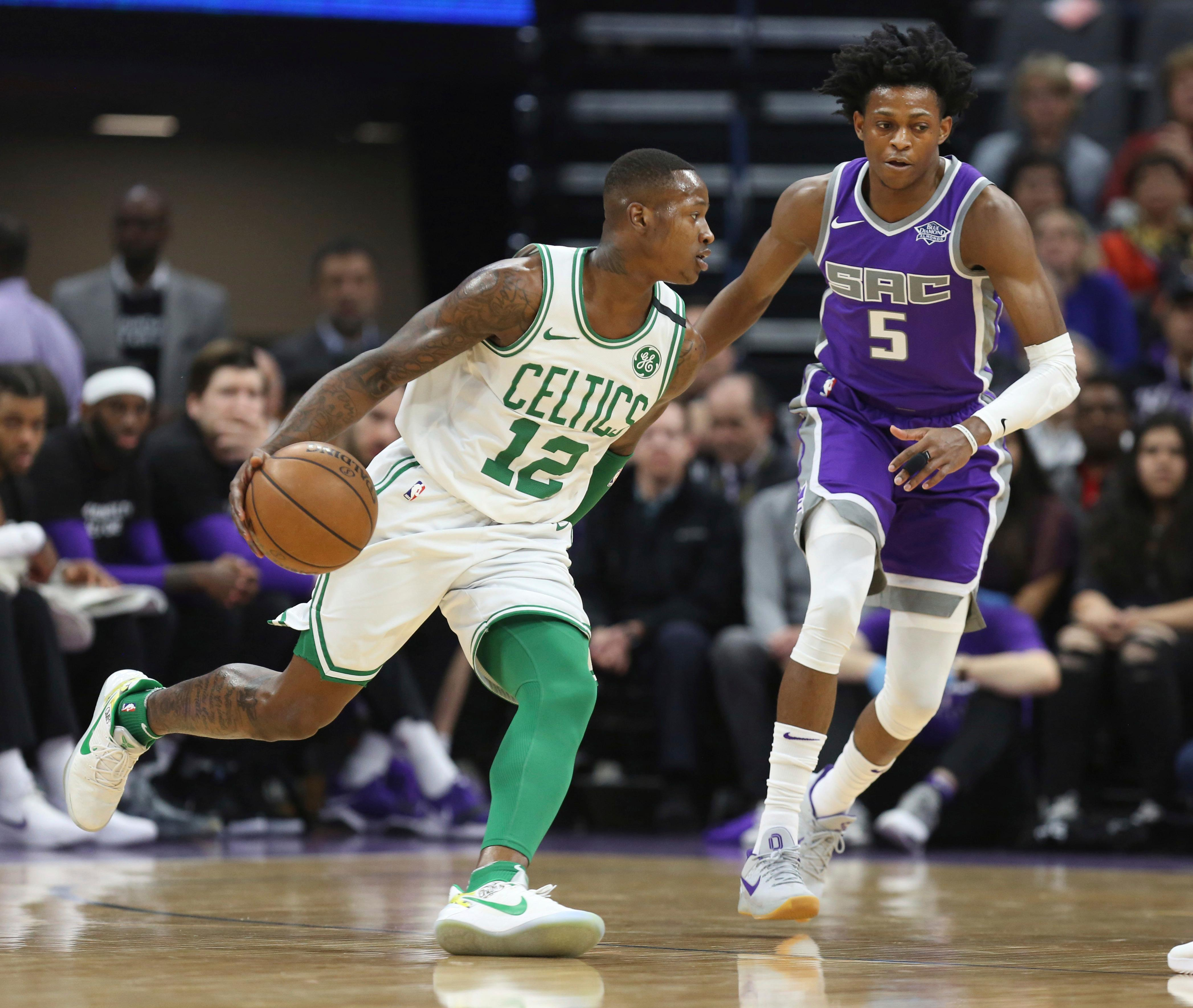 Boston Celtics guard Terry Rozier (12) drives around Sacramento Kings guard De'Aaron Fox (5) during the first half of an NBA basketball game in Sacramento, Calif., Sunday, March 25, 2018. (AP Photo/Steve Yeater)