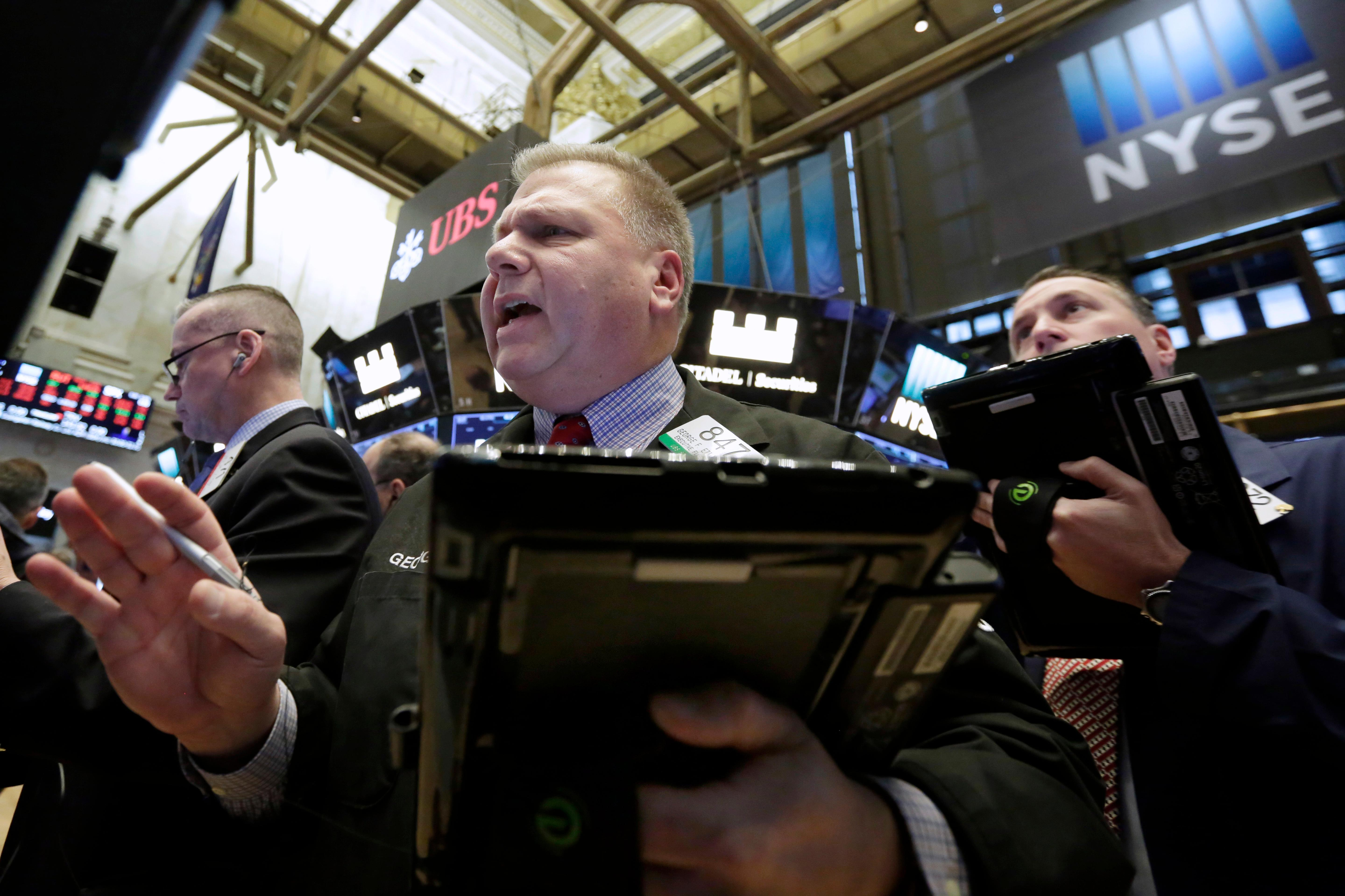 Trader George Ettinger, center, works on the floor of the New York Stock Exchange, Tuesday, Feb. 6, 2018. The Dow Jones industrial average fell as much as 500 points in early trading, bringing the index down 10 percent from the record high it reached on Jan. 26. The DJIA quickly recovered much of that loss. (AP Photo/Richard Drew)