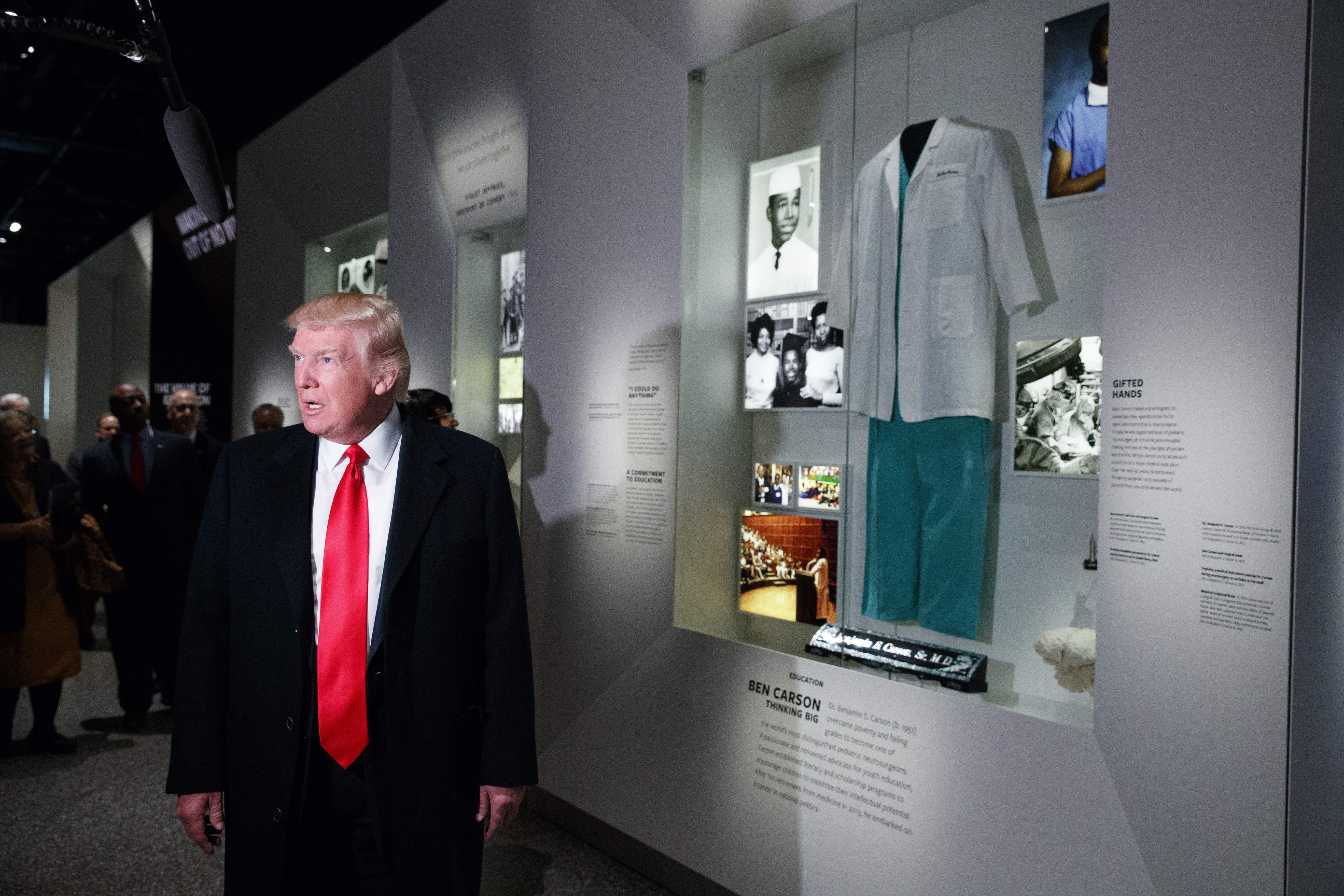 DAY 33 - In this Feb. 21, 2017, file photo, President Donald Trump talks with reporters as he stops at the exhibit for Dr. Ben Carson, his nominee for Housing and Urban Development secretary, during a tour of the National Museum of African American History and Culture in Washington. (AP Photo/Evan Vucci, File)
