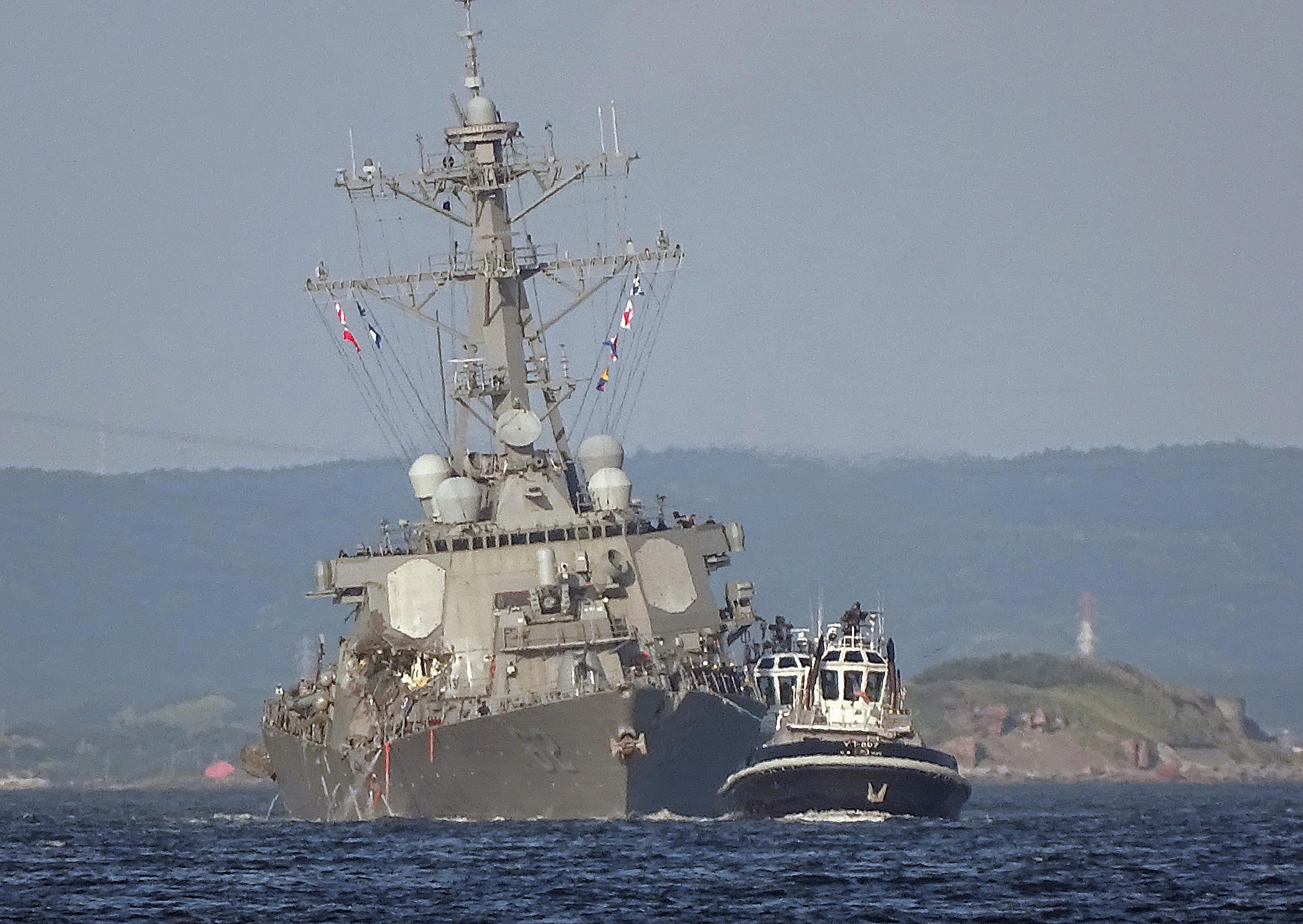The damaged USS Fitzgerald is being towed by a tugboat in the waters near the U.S. Naval base in Yokosuka, southwest of Tokyo, after the U.S. destroyer collided with the Philippine-registered container ship ACX Crystal in the waters off the Izu Peninsula Saturday, June 17, 2017. The USS Fitzgerald was back at its home port in Japan after colliding before dawn Saturday with the container ship four times its size, while the coast guard and Japanese and U.S. military searched for seven sailors missing after the crash. (AP Photo/Eugene Hoshiko)