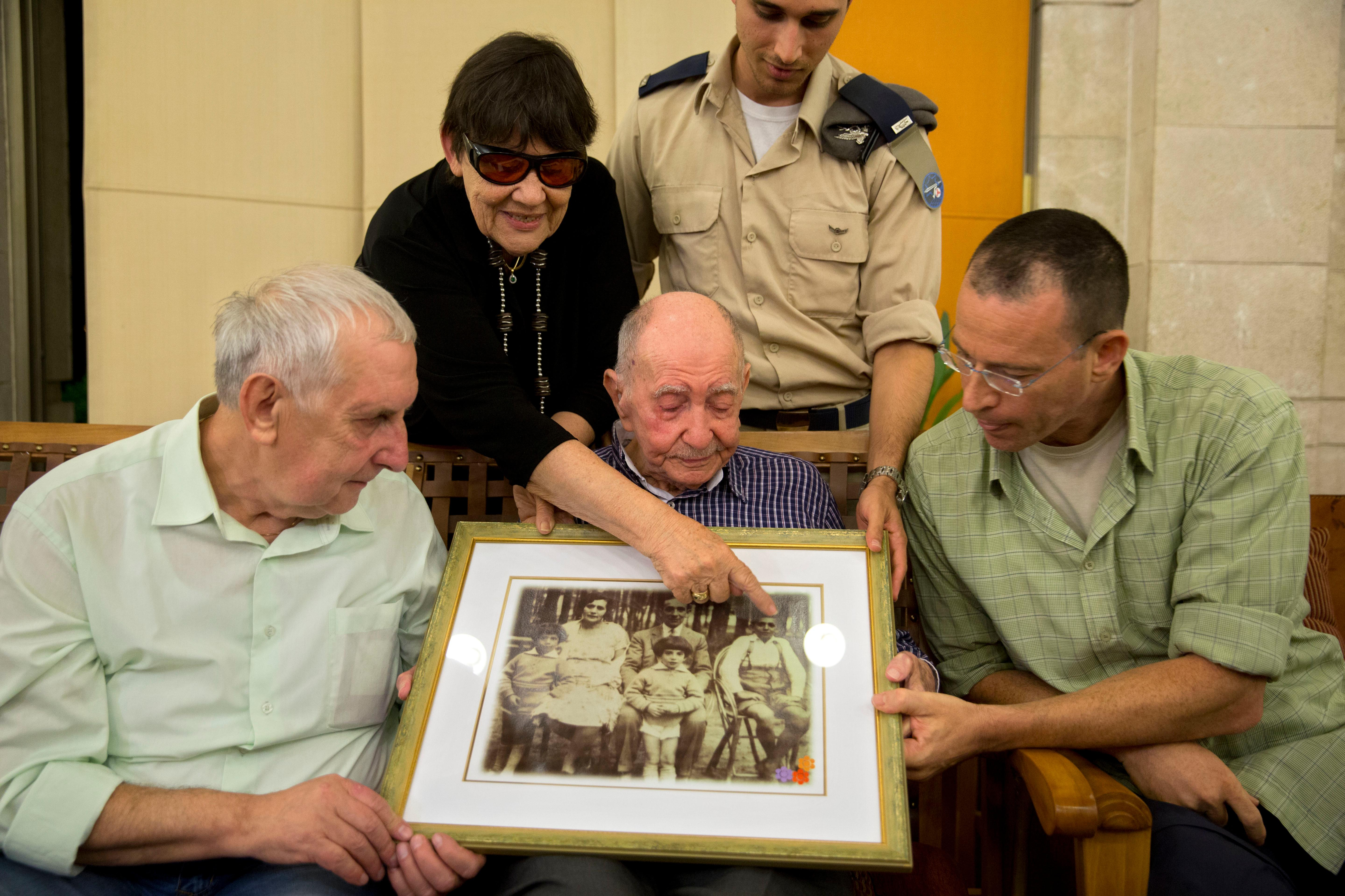 In this Thursday, Nov. 16, 2017 photo, Israeli Holocaust survivor Eliahu Pietruszka, center, looks at a picture with Alexandre Pietruszka and family in the central Israeli city of Kfar Saba. Pietruszka who fled Poland at the beginning of World War II and thought his entire family had perished learned that a younger brother had also survived, and his son, 66-year-old Alexandre, flew from Russia to see him. (AP Photo/Sebastian Scheiner)