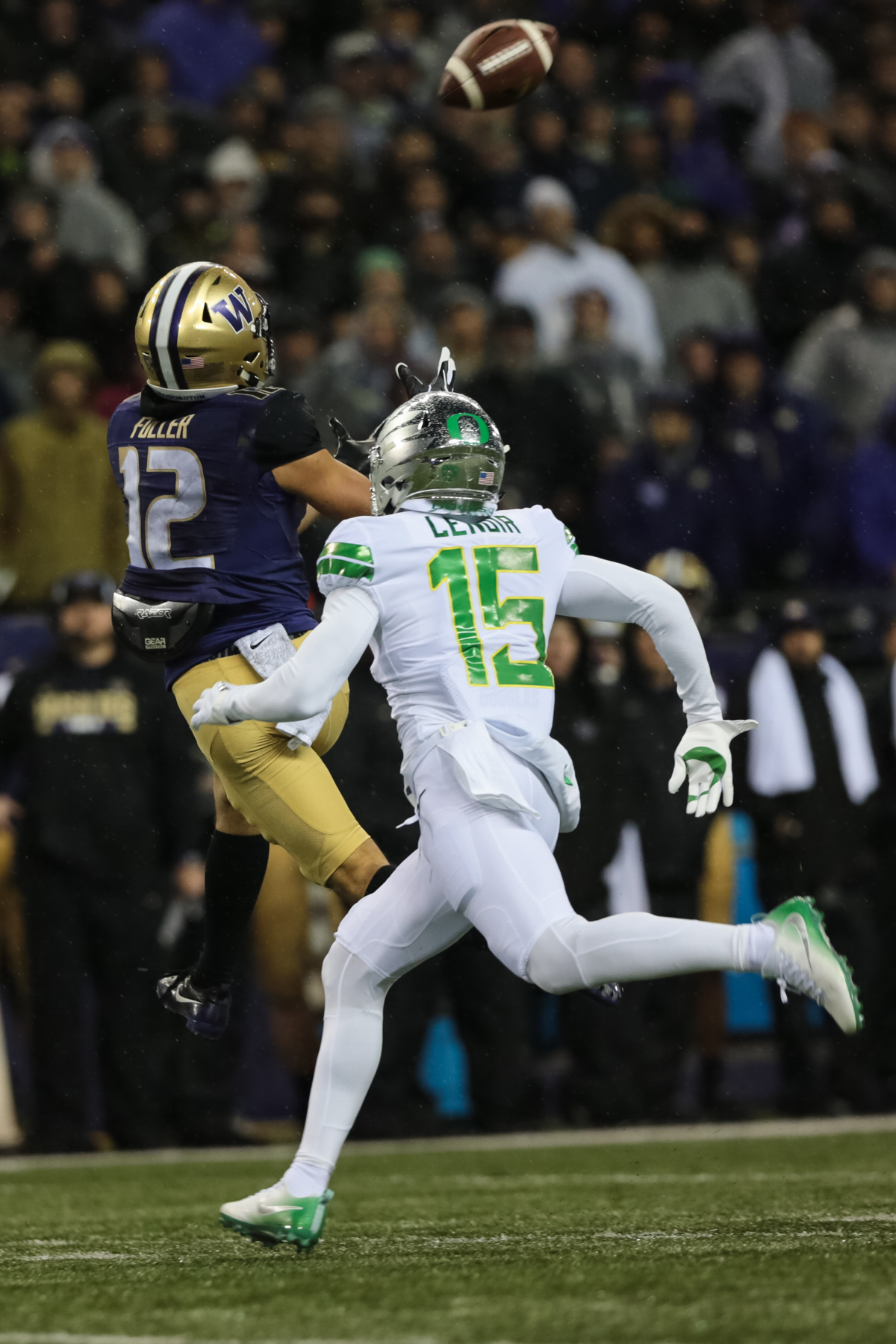 Washington wide receiver Aaron Fuller (#21) goes up to catch a pass while covered by Oregon cornerback Deommodore Lenoir (#15). The Oregon Ducks are trailing the Washington Huskies 3 - 17 at halftime.  The Huskies rallied with a 17-point second quarter after a slow first quarter on a cold and rainy night in Seattle, Washington.  Photo by Austin Hicks, Oregon News Lab