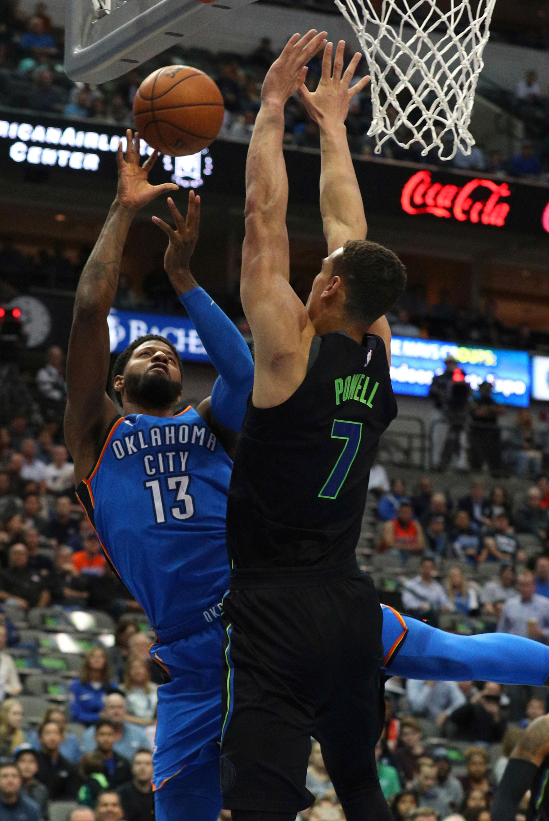Oklahoma City Thunder forward Paul George (13) tries to put up a shot against Dallas Mavericks forward Dwight Powell (7) during the first half of an NBA basketball game Wednesday, Feb. 28, 2018 in Dallas. (AP Photo/ Richard W. Rodriguez)