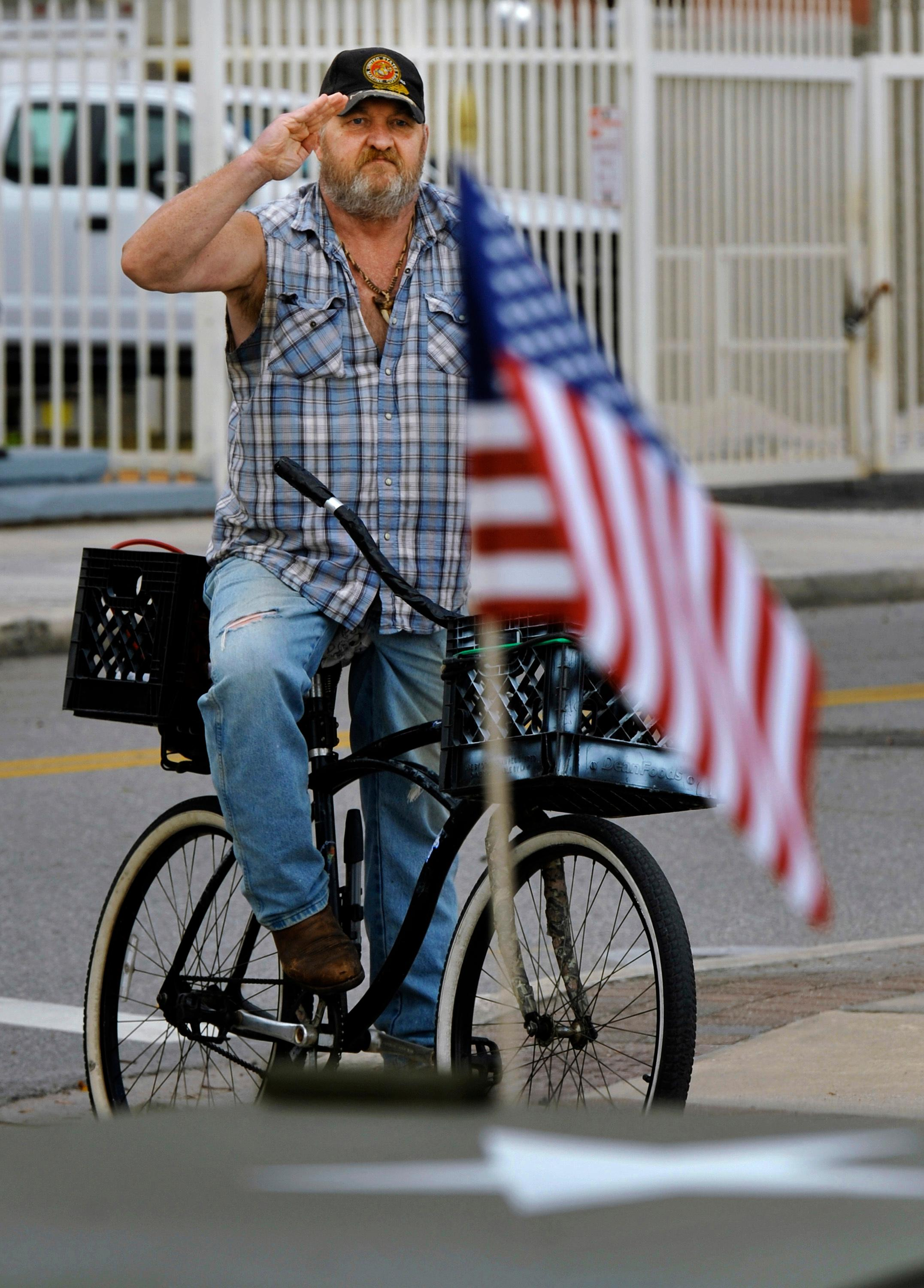 Wearing a U.S. Marine Corps ball cap Jacksonville resident Bill Smith salutes a vintage military jeep decorated with American Flags as he watches the Veterans Day parade, Saturday Nov. 11, 2017, in Jacksonville, Fla. Smith, who did not serve in the military himself, said he comes out and salutes for his brother who died serving in Vietnam with the Marine Corps. (Bob Self/The Florida Times-Union via AP)