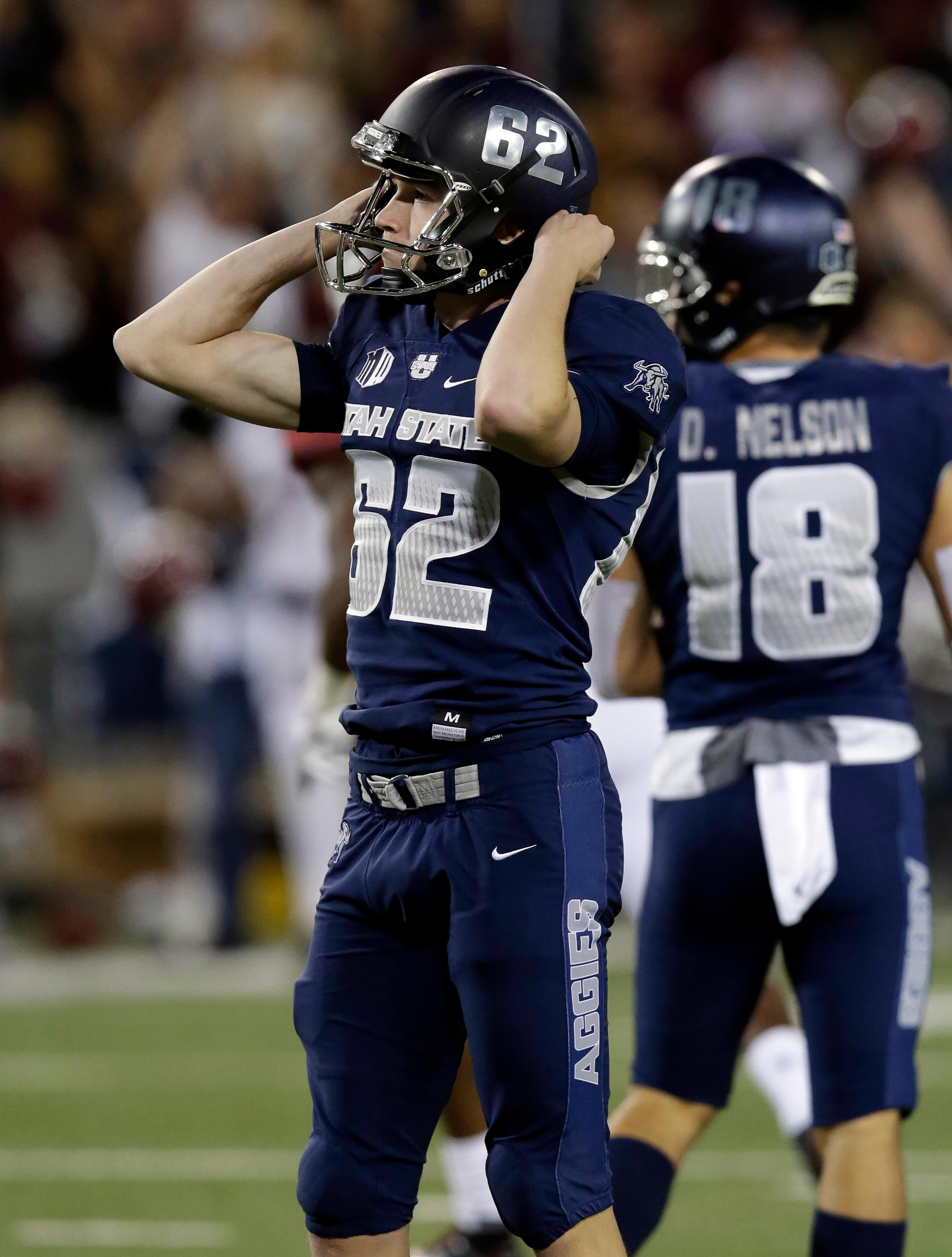 Utah State placekicker Dominik Eberle (62) reacts after missing a field goal in overtime against New Mexico State during the Arizona Bowl NCAA college football game, Friday, Dec. 29, 2017, in Tucson, Ariz. (AP Photo/Rick Scuteri)