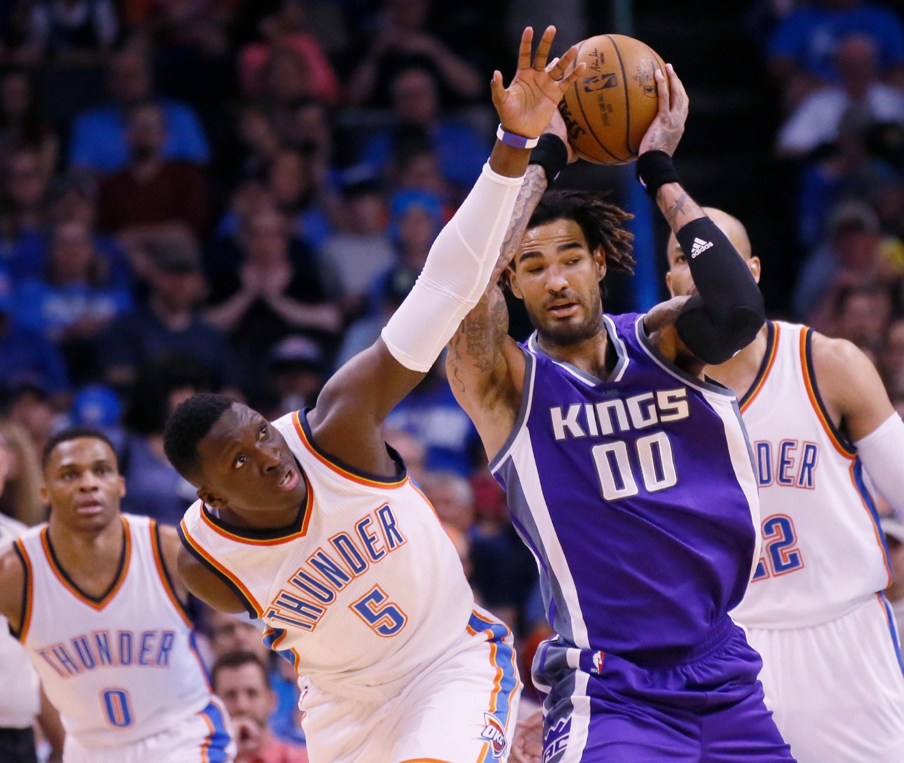 Oklahoma City Thunder guard Victor Oladipo (5) reaches for the ball held by Sacramento Kings center Willie Cauley-Stein (00) in the first quarter of an NBA basketball game in Oklahoma City, Saturday, March 18, 2017. (AP Photo/Sue Ogrocki)