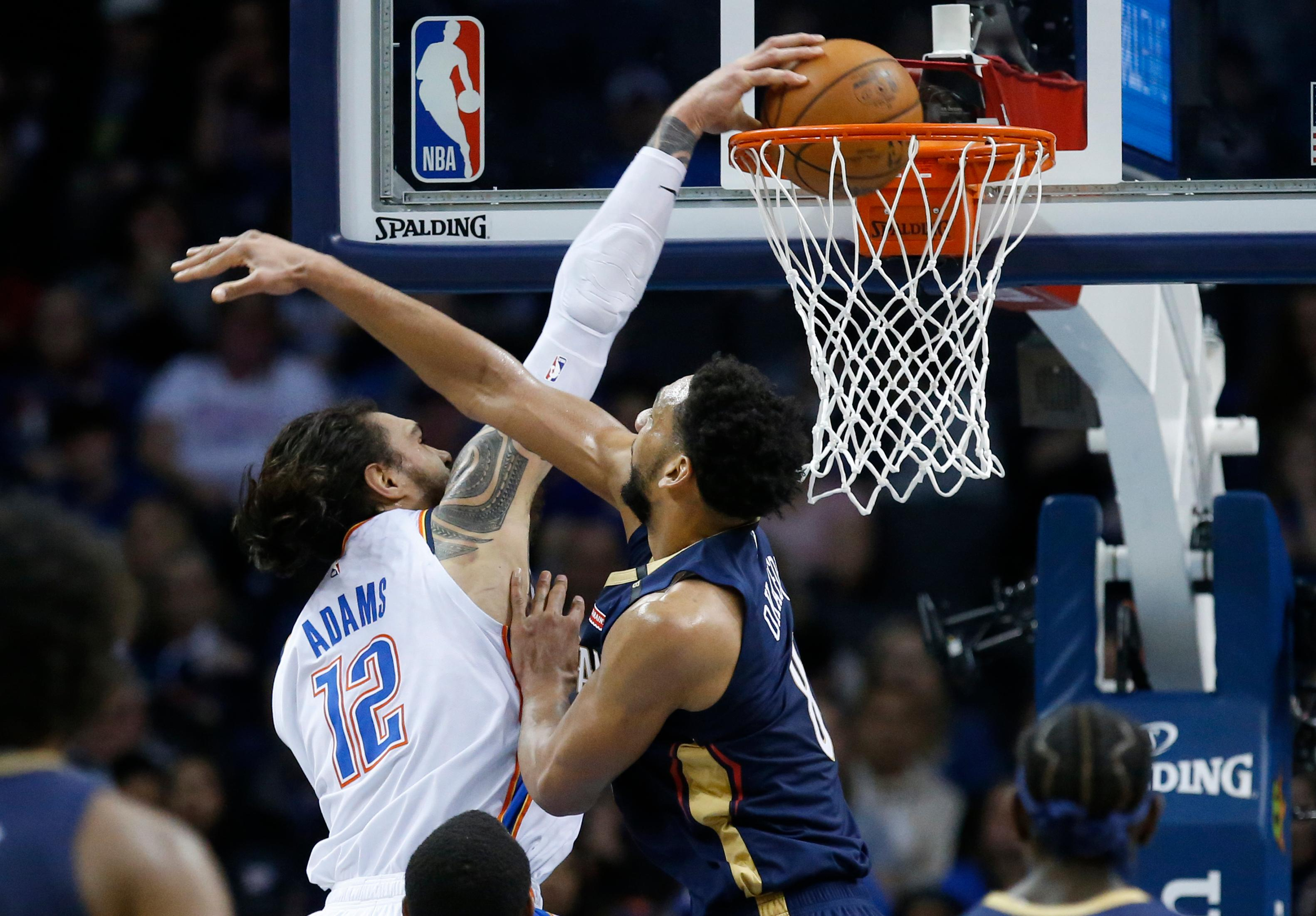 Oklahoma City Thunder center Steven Adams (12) dunks next to New Orleans Pelicans center Jahlil Okafor (8) during the first half of an NBA basketball game in Oklahoma City, Thursday, Jan. 24, 2019. (AP Photo/Sue Ogrocki)