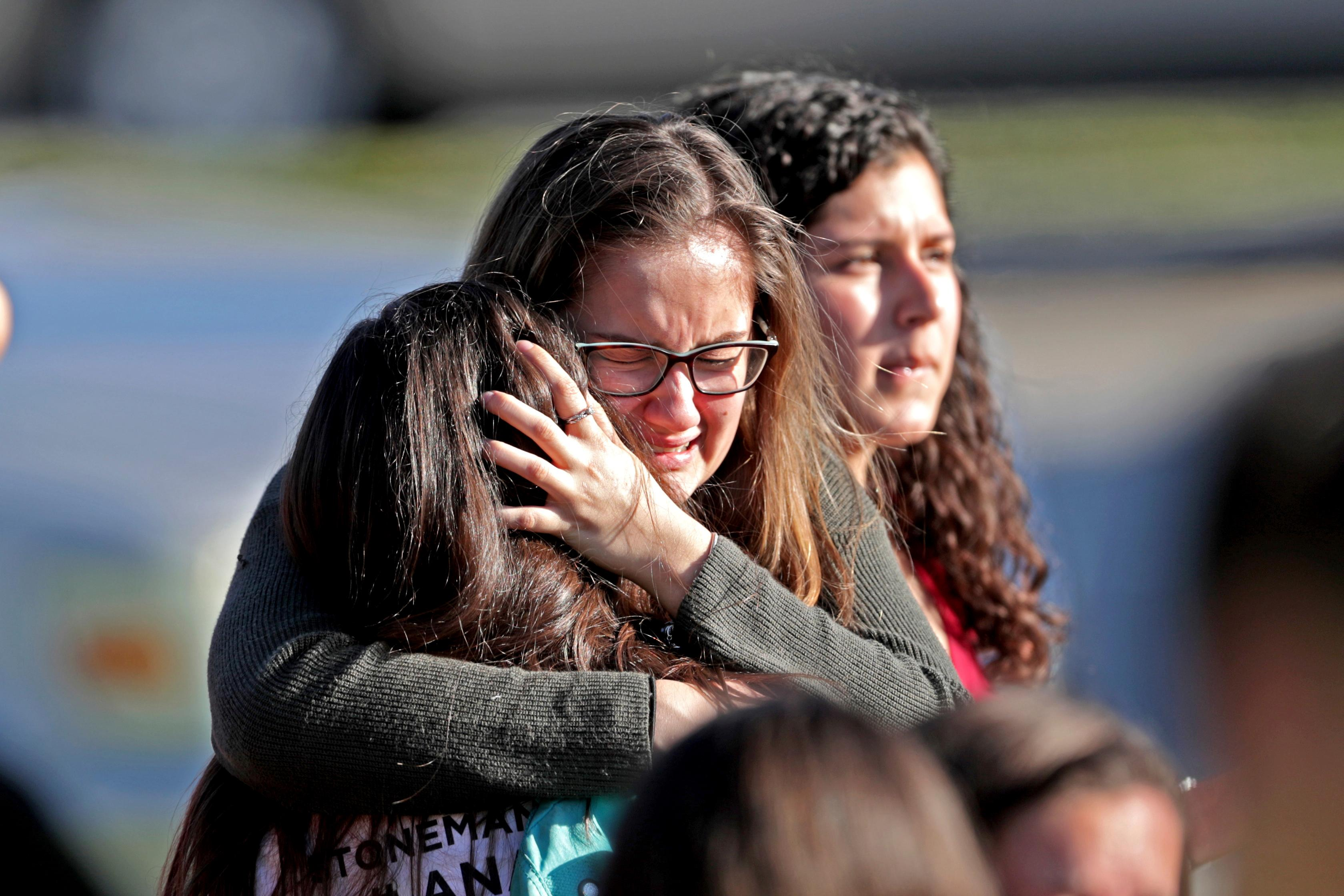 FILE - In this Wednesday, Feb. 14, 2018 file photo, students released from a lockdown embrace following a shooting at Marjory Stoneman Douglas High School in Parkland, Fla. A week after a shooter slaughtered more than a dozen people in the Florida high school, thousands of protesters, including many angry teenagers, swarmed into the state Capitol on Wednesday, Feb. 21, calling for changes to gun laws, a ban on assault-type weapons and improved care for the mentally ill. (John McCall/South Florida Sun-Sentinel via AP, File)