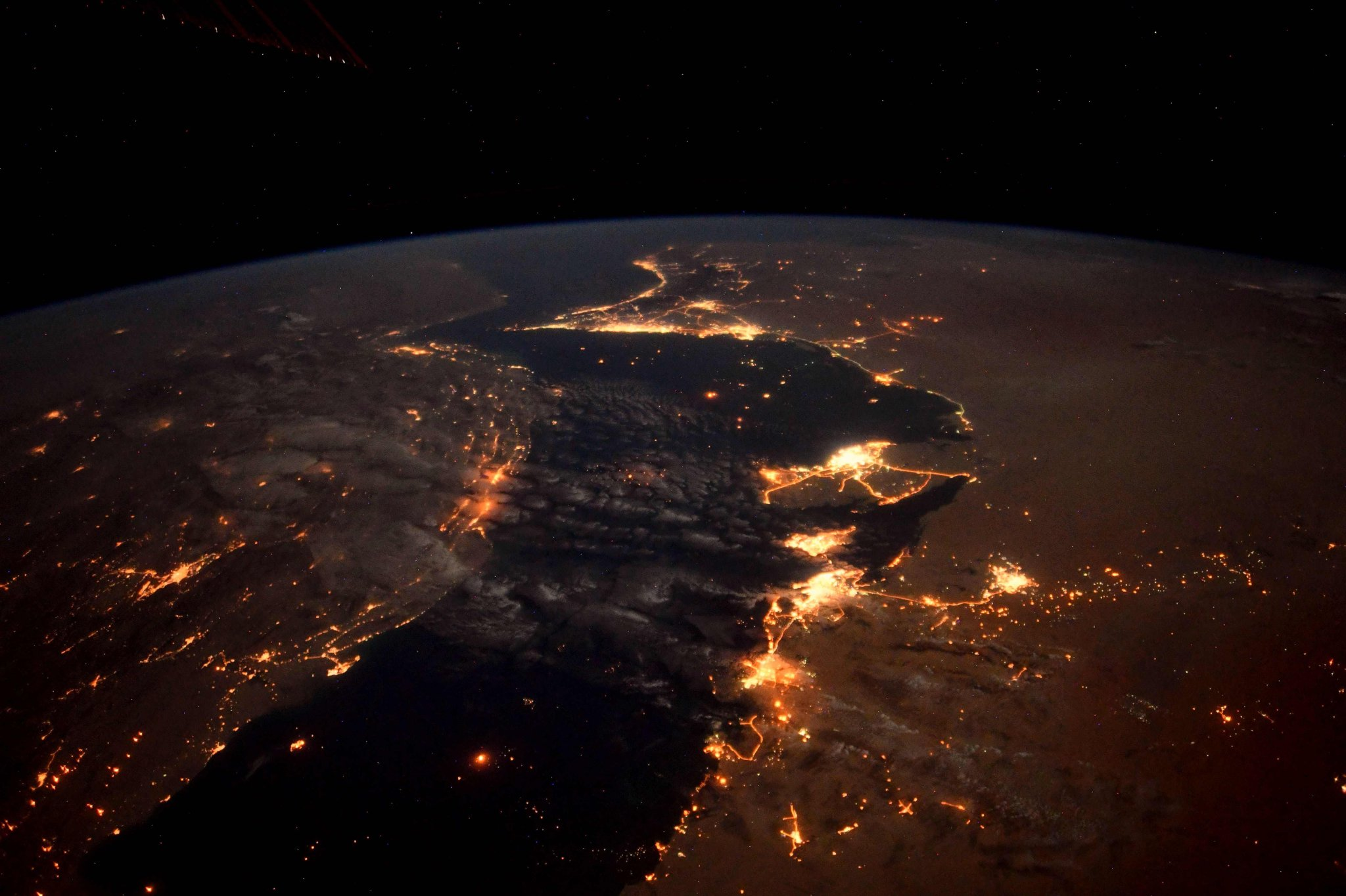 Even the dark of night cannot subdue the rich hues of the desert bordering the Persian Gulf. #Qatar #Dubai #AbuDhabi #Oman #Iran #SaudiArabia #Bahrain #UAE (Photo & Caption: Ricky Arnold / NASA)