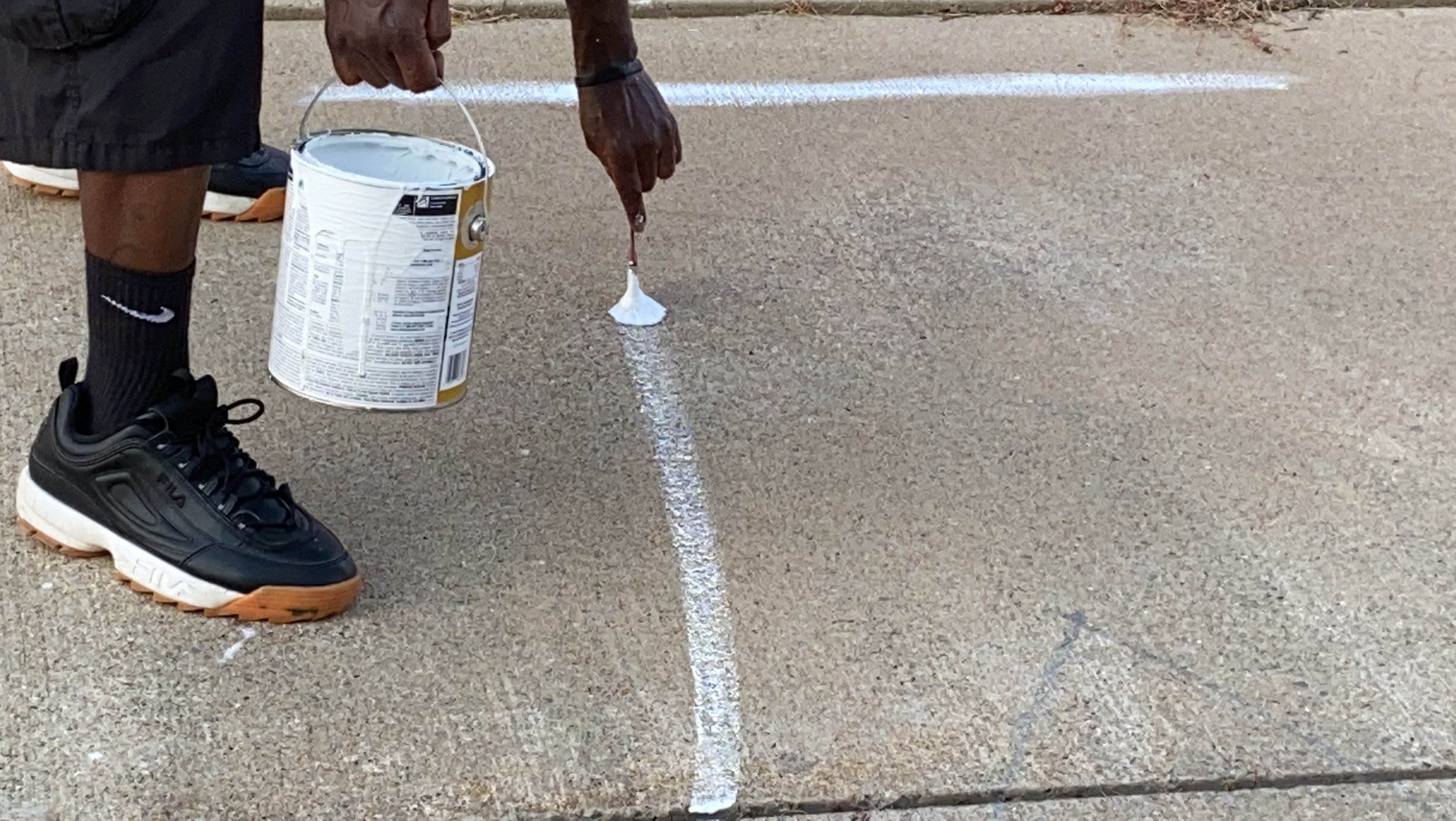 Less than one gallon of white paint is used to create the words on the sidewalk for the mural project Tuesday, July 7, 2020. (WWMT/Jason Heeres)