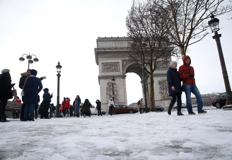 Tourists stroll on the snow-covered Champs Elysees avenue near the Arc de Triomphe in Paris, France, Friday, Feb. 9, 2018. The Eiffel Tower is closed and authorities are telling drivers in the Paris region to stay home as snow and freezing rain have hit a swath of France ill-prepared for the wintry weather. (AP Photo/Michel Euler)