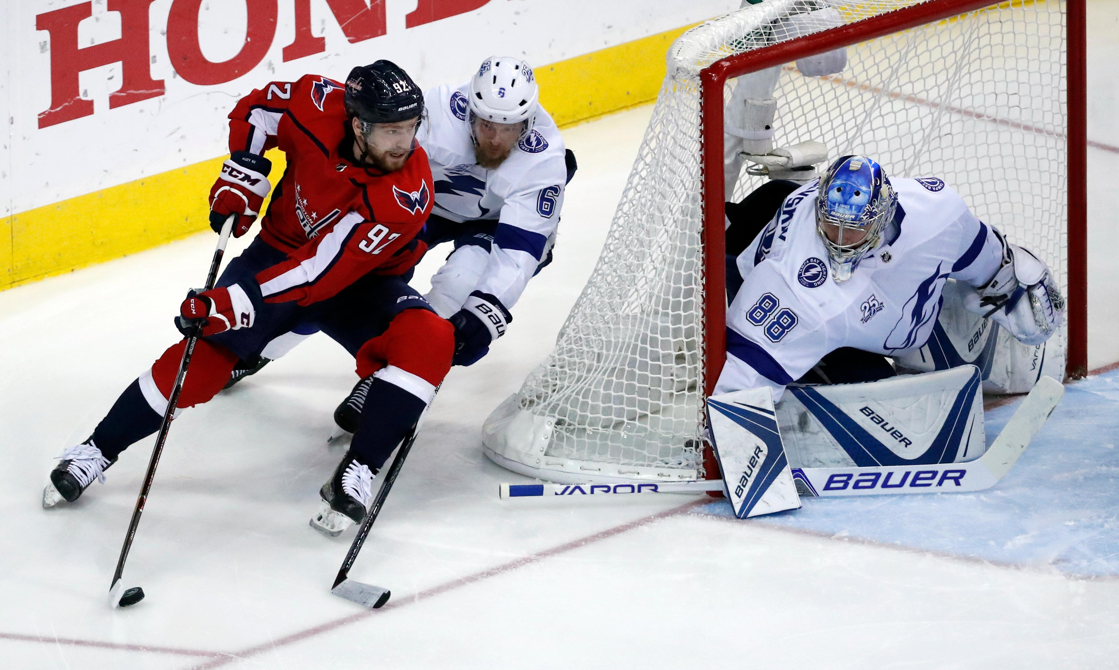 Washington Capitals center Evgeny Kuznetsov (92), from Russia, skates with the puck with Tampa Bay Lightning defenseman Anton Stralman (6), from Sweden, behind him with Tampa Bay Lightning goaltender Andrei Vasilevskiy (88), from Russia, in goal during the second period of Game 6 of the NHL Eastern Conference finals hockey playoff series, Monday, May 21, 2018, in Washington. (AP Photo/Alex Brandon)