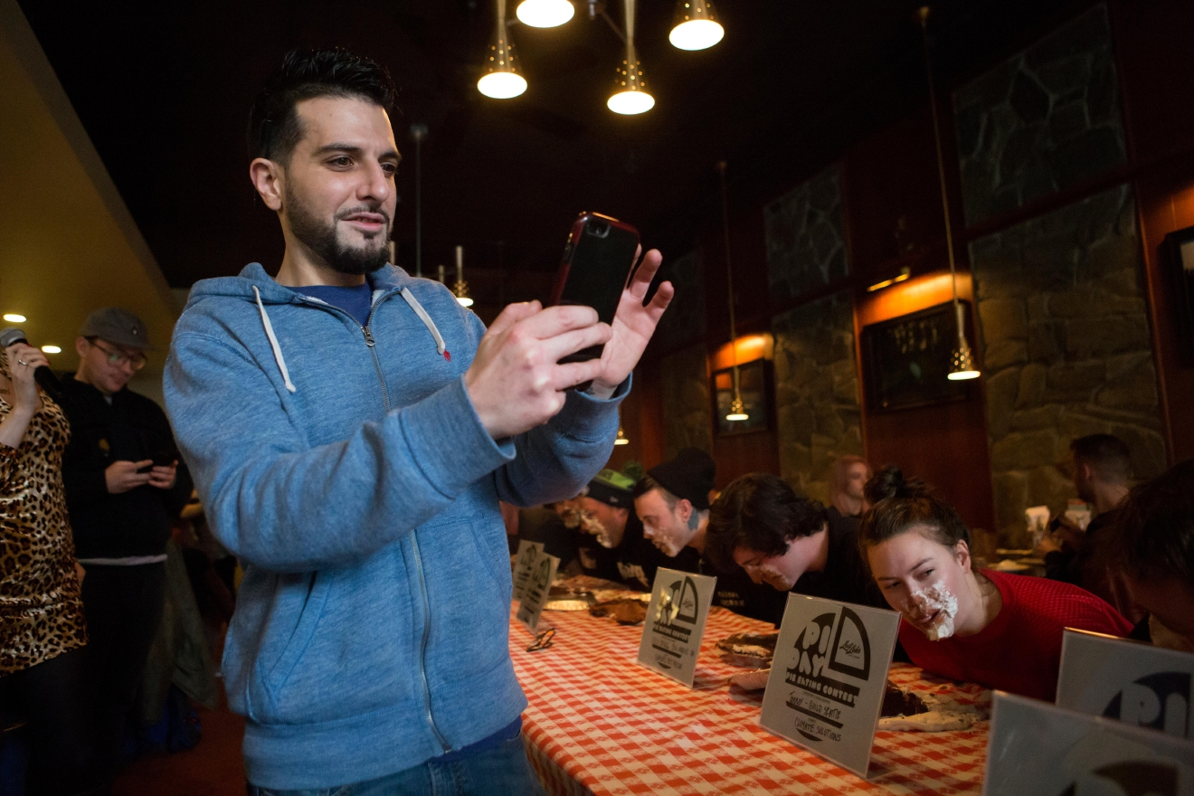 Ioannis Kalogiros from Poquitos takes photos of contestants racing to finish their pies during the second annual Pi Day Pie Eating Contest at Lost Lake Cafe. (Sy Bean / Seattle Refined)