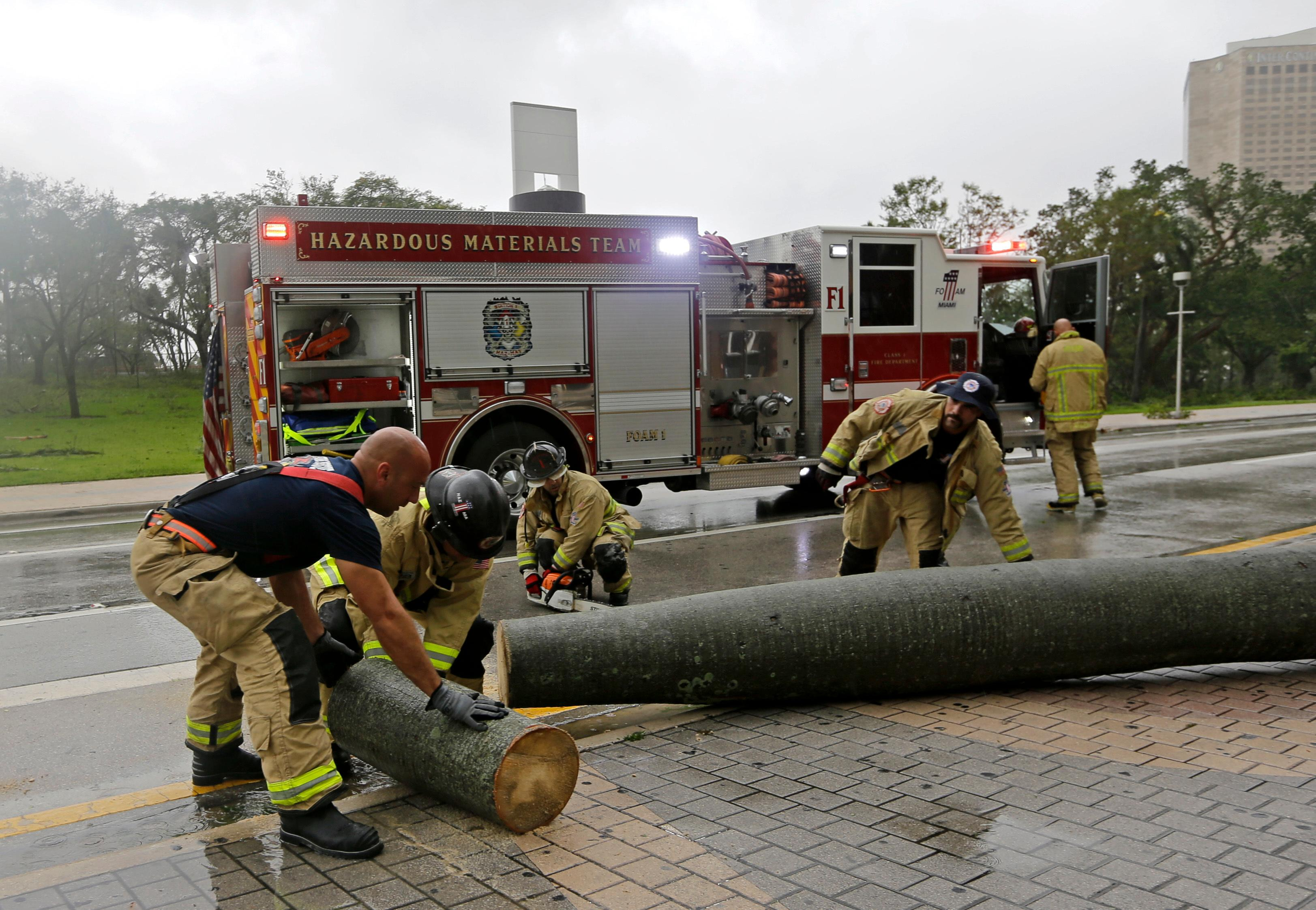 A City of Miami Fire and Rescue crew cuts up a fallen palm tree during Hurricane Irma, as they clear the street, Sunday, Sept. 10, 2017, in downtown Miami. (AP Photo/Alan Diaz)
