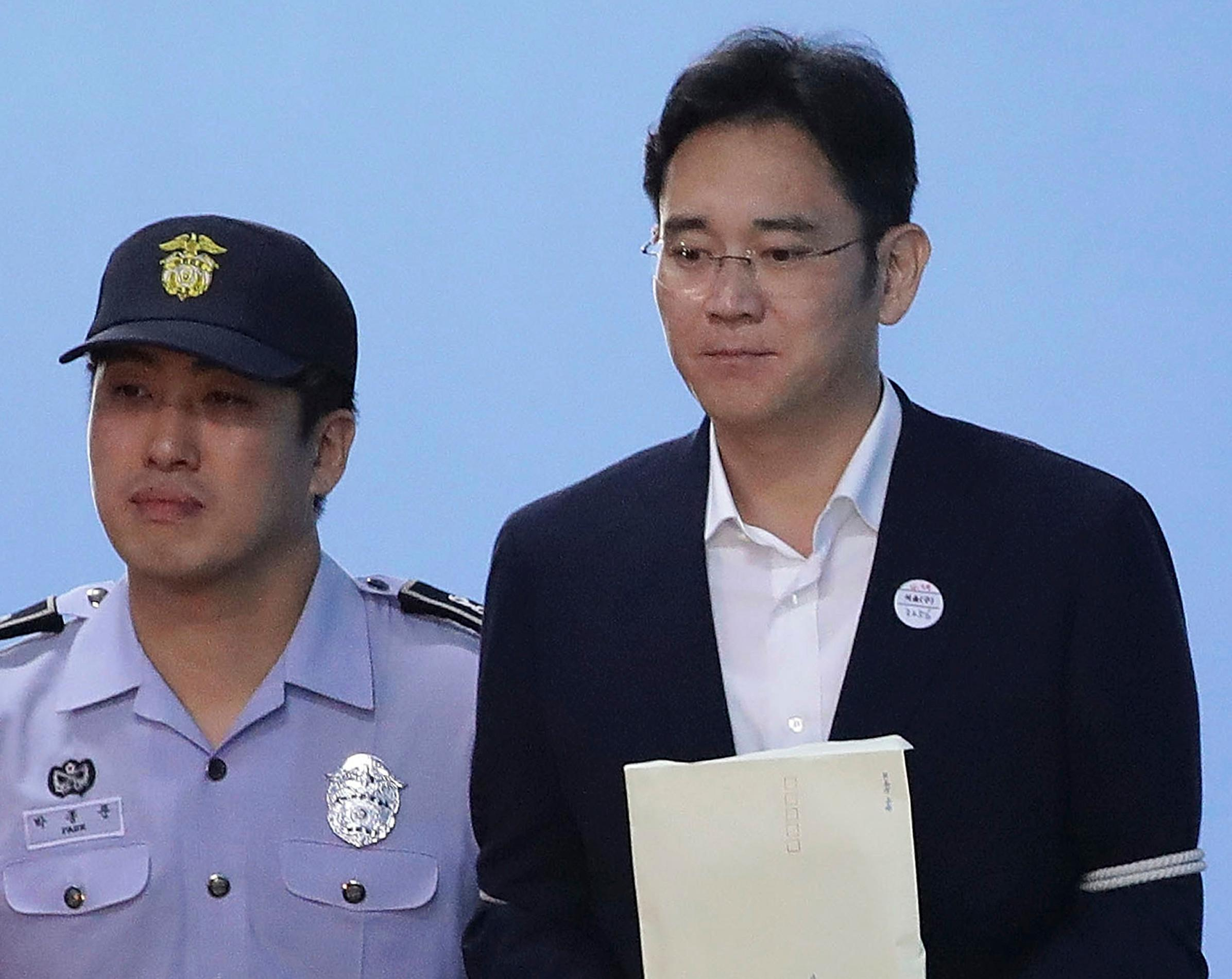 Samsung Electronics Co. Vice Chairman Lee Jae-yong, right, leaves after his verdict trial at the Seoul Central District Court Friday, Aug. 25, 2017 in Seoul, South Korea. The court sentenced the billionaire Samsung heir to five years in prison for bribery and other crimes that fed public anger leading to the ouster of Park Geun-hye as South Korea's president. (Chung Sung-Jun/Pool Photo via AP)