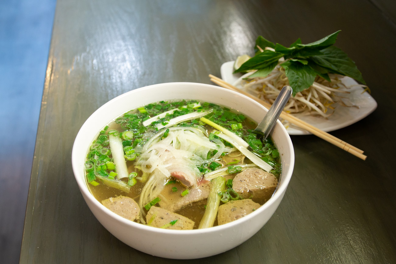 Pho (their most popular dish) is a traditional Vietnamese soup made with rice noodles in a delicately flavored chicken or beef broth, garnished with yellow onions, cilantro, and green onions and served with a side of basil, bean sprouts, lime, and jalapenos. Customers get a choice of beef pho with eye round steak and beef meatballs, or chicken pho with chicken breast meat. / Image: Elizabeth A. Lowry // Published: 1.2.20