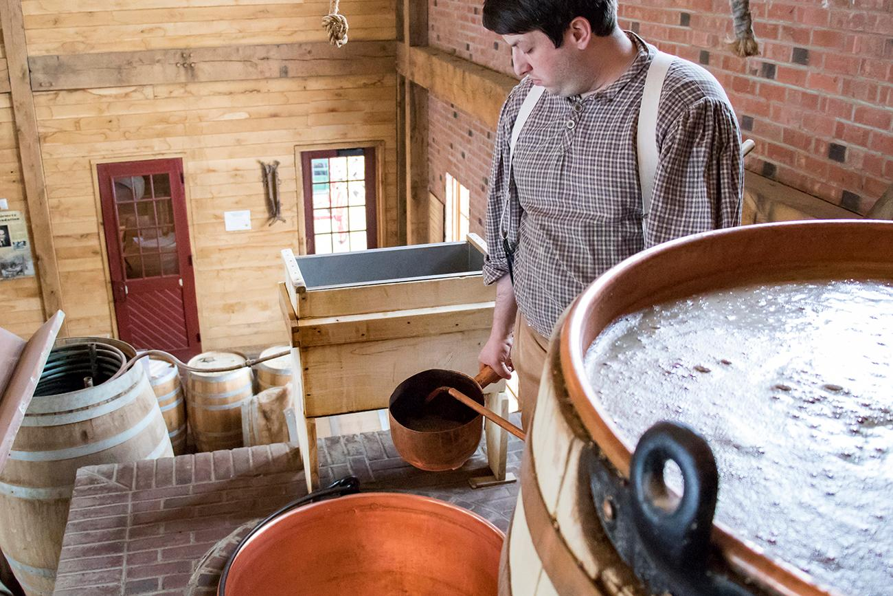 Milled malt steeps in the hot water to draw its sugars out into the water. The sugary water is called wort. Head Brewer, Kyle Spears, is shown hand ladling the wort. / Image: Allison McAdams