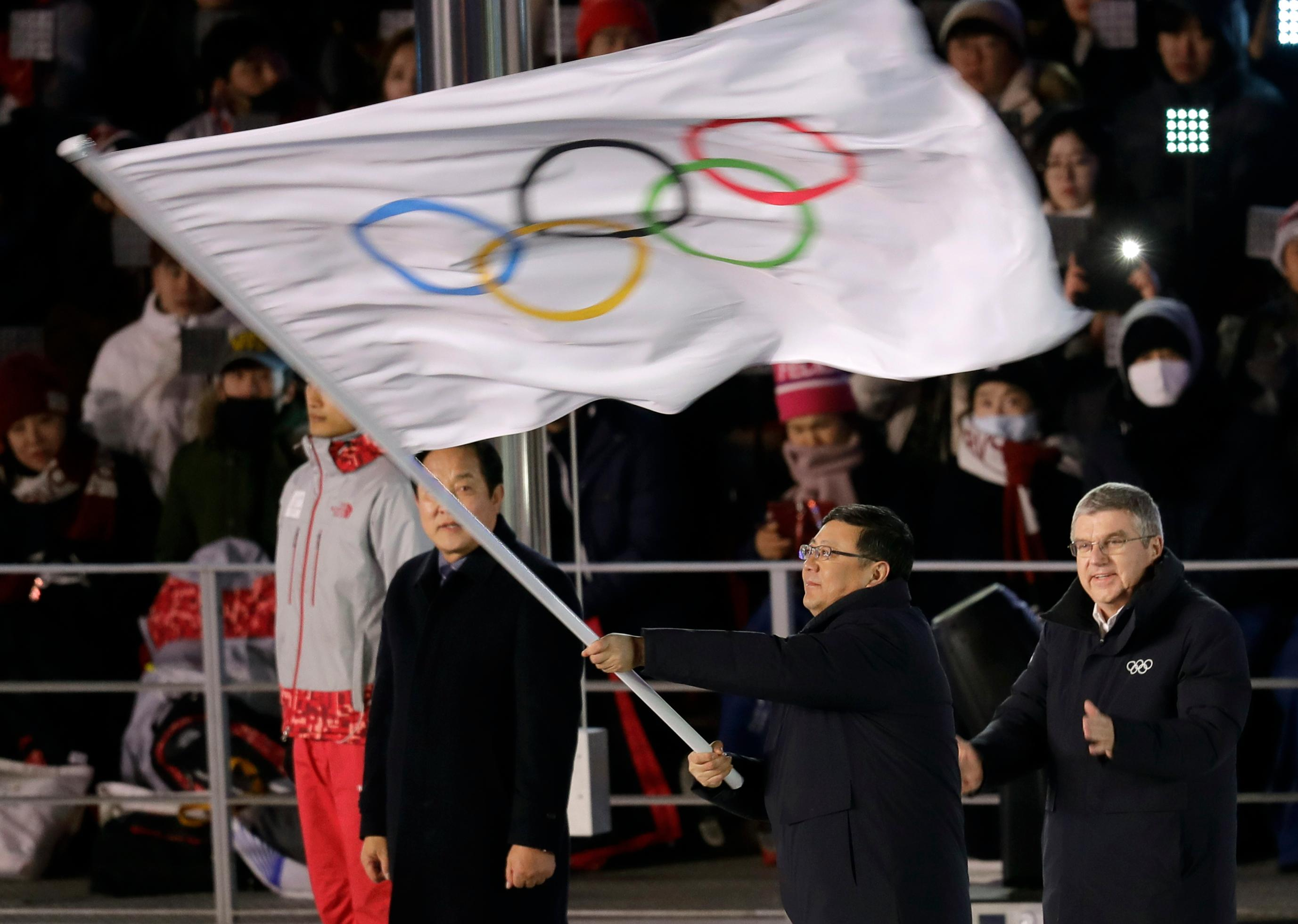 Chen Jining, mayor of Beijing waves the Olympic flag as Thomas Bach, president of the International Olympic Committee watches during the closing ceremony of the 2018 Winter Olympics in Pyeongchang, South Korea, Sunday, Feb. 25, 2018. (AP Photo/Michael Probst)