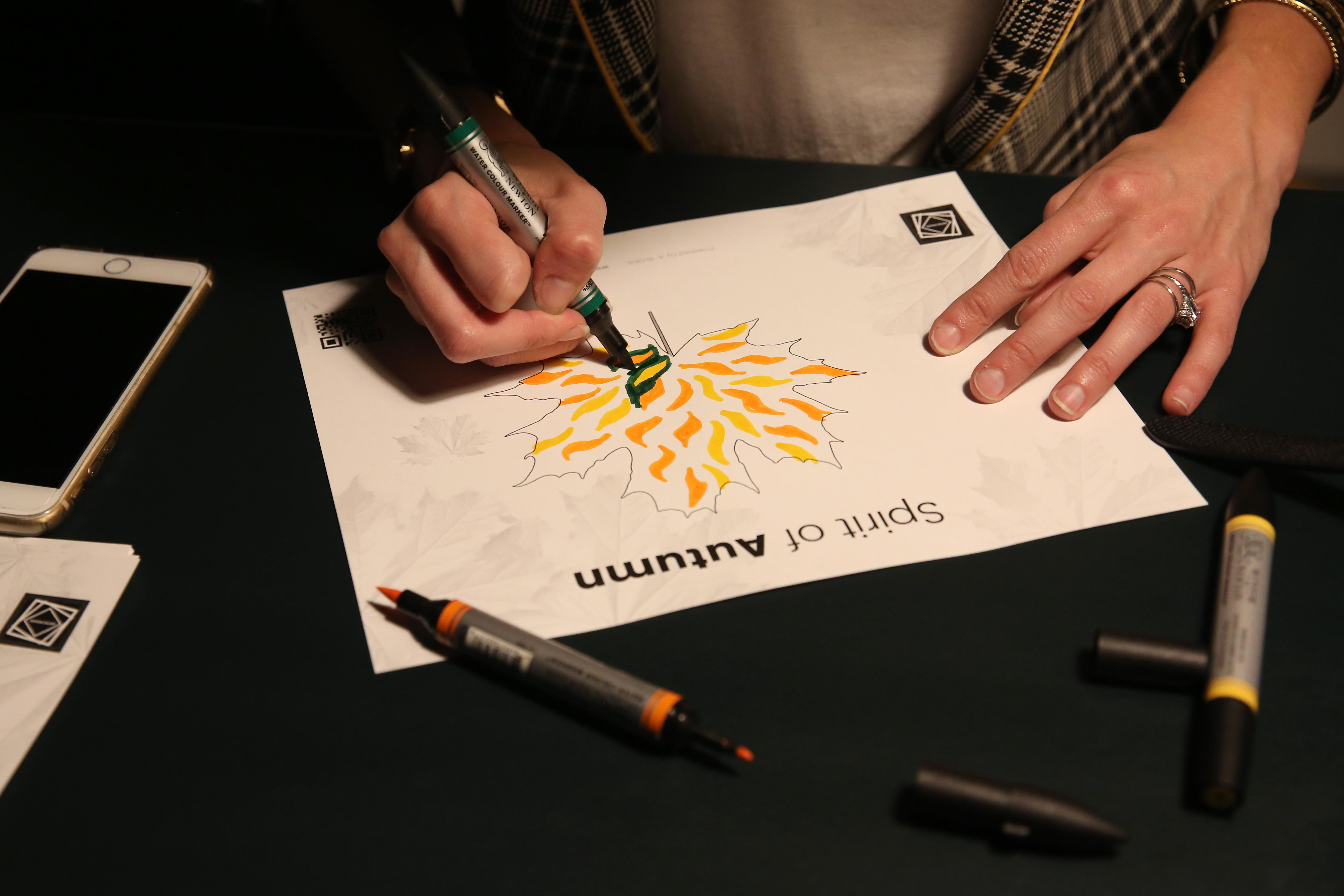 Visitors draw on leaves which are then digitally inserted into the exhibit. (Amanda Andrade-Rhoades/DC Refined)