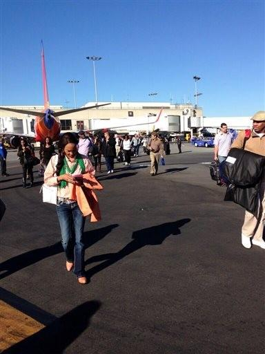 In this photo provided by Natalie Morin, people stand on the tarmac after being evacuated from Los Angeles International Airport, Friday.