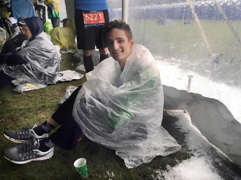Connor Buchholz, 25, of Toledo, Ohio, waits under a tent beside ice crystals that accumulated at the athlete's village, before the precipitation turned to rain, before the start of the the 122nd Boston Marathon on Monday, April 16, 2018, in Hopkinton, Mass. (AP Photo/Jennifer McDermott)