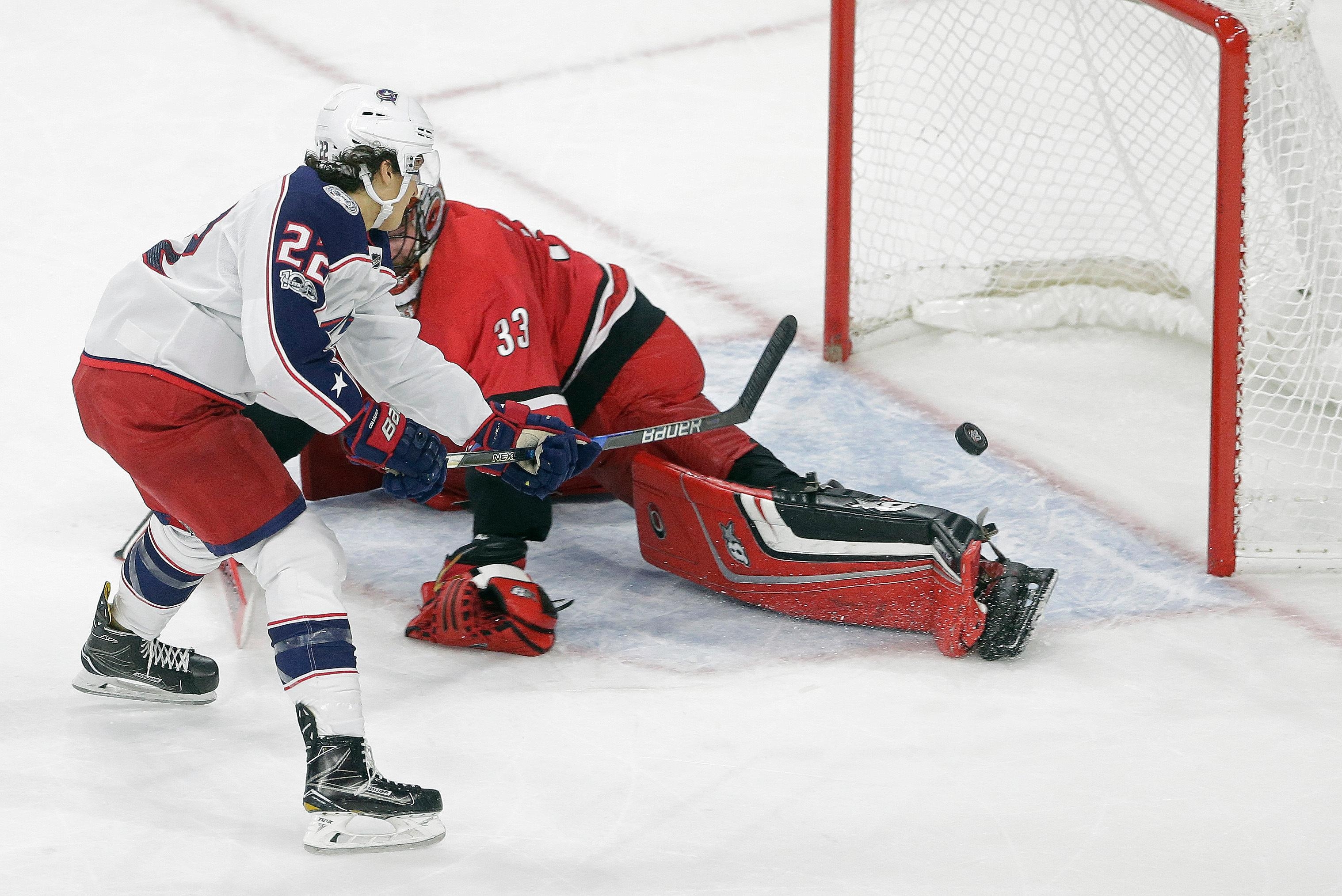 Columbus Blue Jackets' Sonny Milano (22) scores the game-winning goal against Carolina Hurricanes goalie Scott Darling during overtime in an NHL hockey game in Raleigh, N.C., Tuesday, Oct. 10, 2017. Columbus won 2-1. (AP Photo/Gerry Broome)