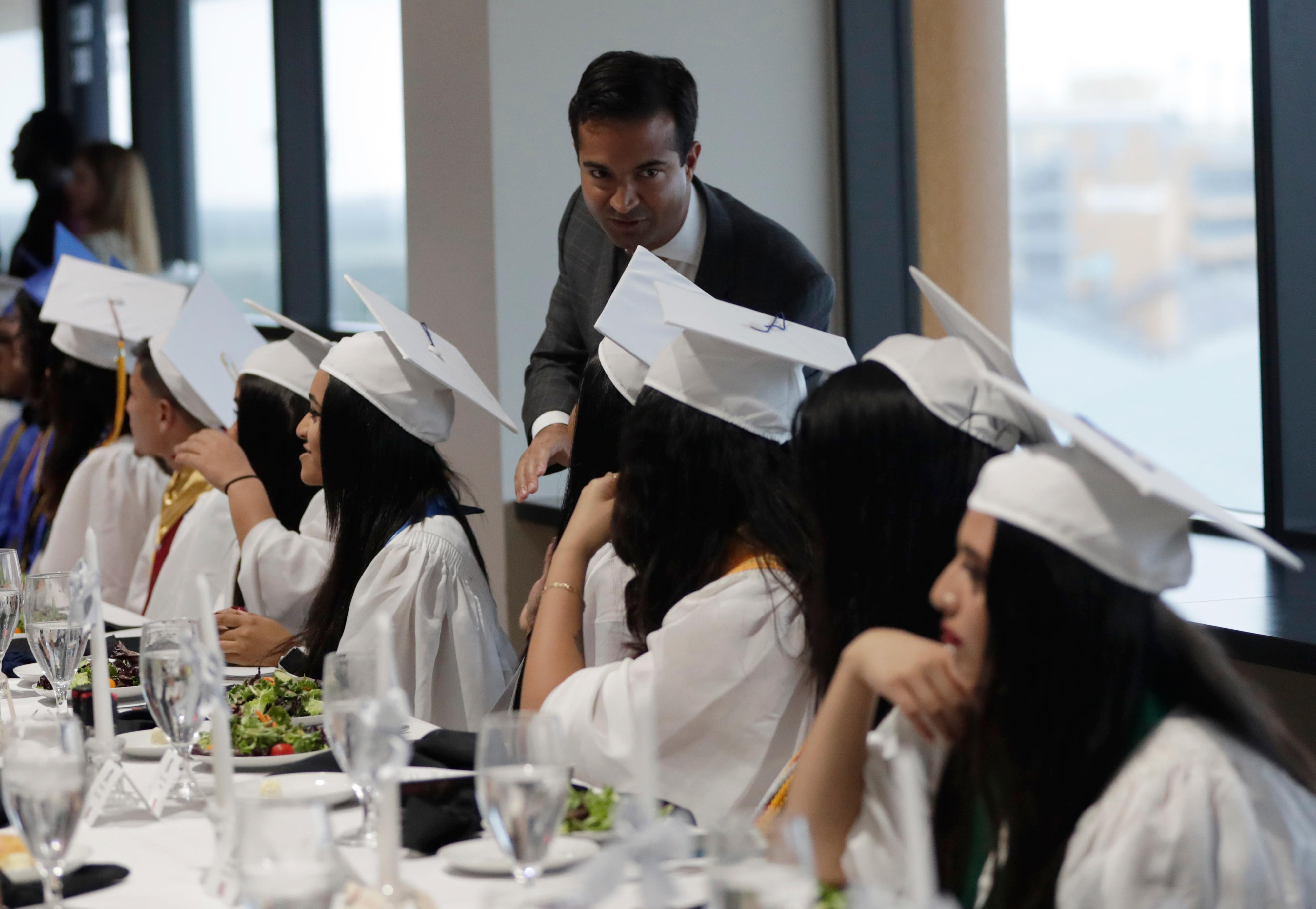 In this Tuesday, May 29, 2018 photo, Rep. Carlos Curbelo, R-Fla., greets graduates while attending the 34th Annual Farmworker Student Recognition Ceremony in Homestead, Fla. (AP Photo/Lynne Sladky)
