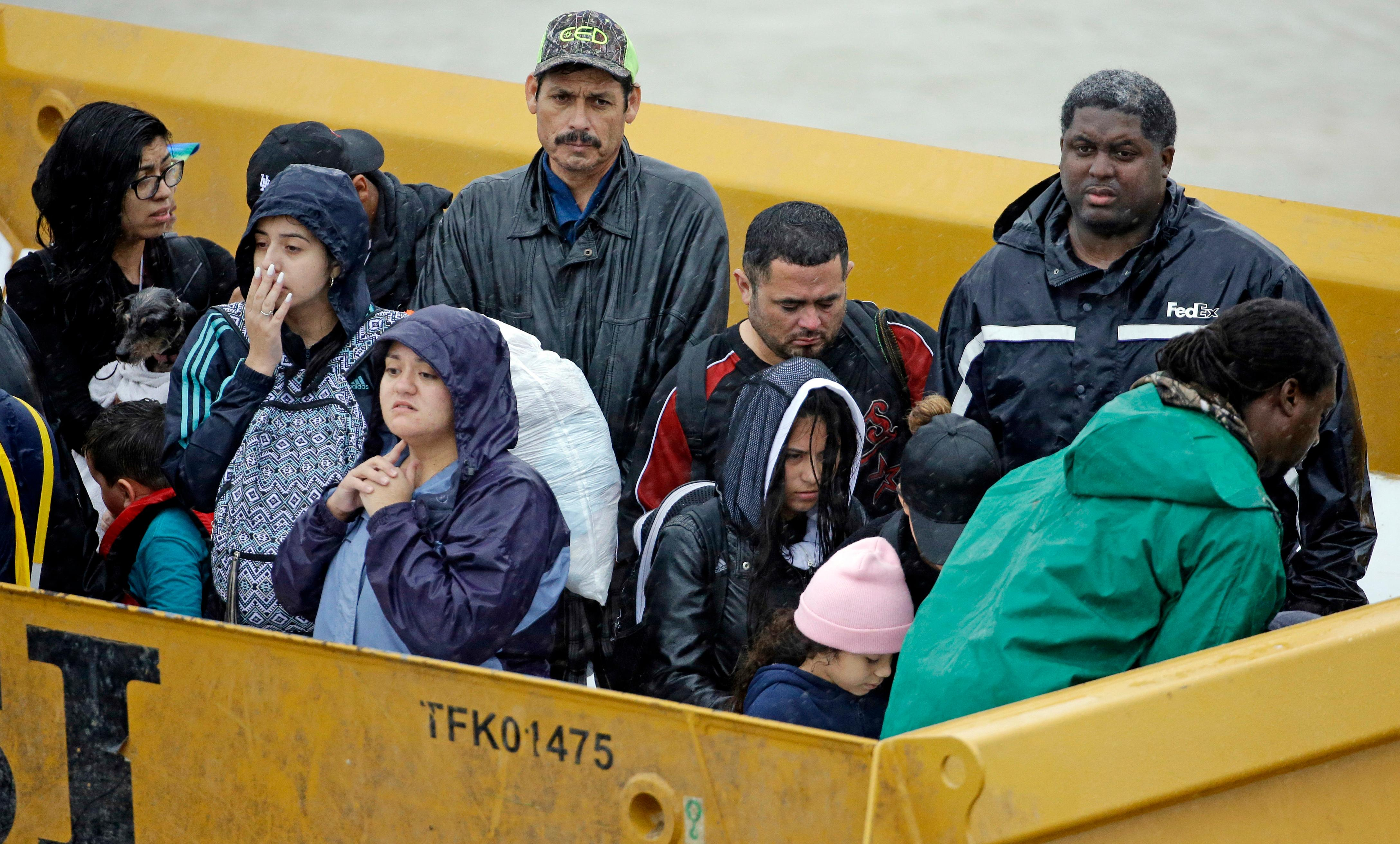 Flood victims wait to unload from the back of a heavy duty truck after being evacuated from their homes as floodwaters from Tropical Storm Harvey rise Monday, Aug. 28, 2017, in Houston. (AP Photo/David J. Phillip)