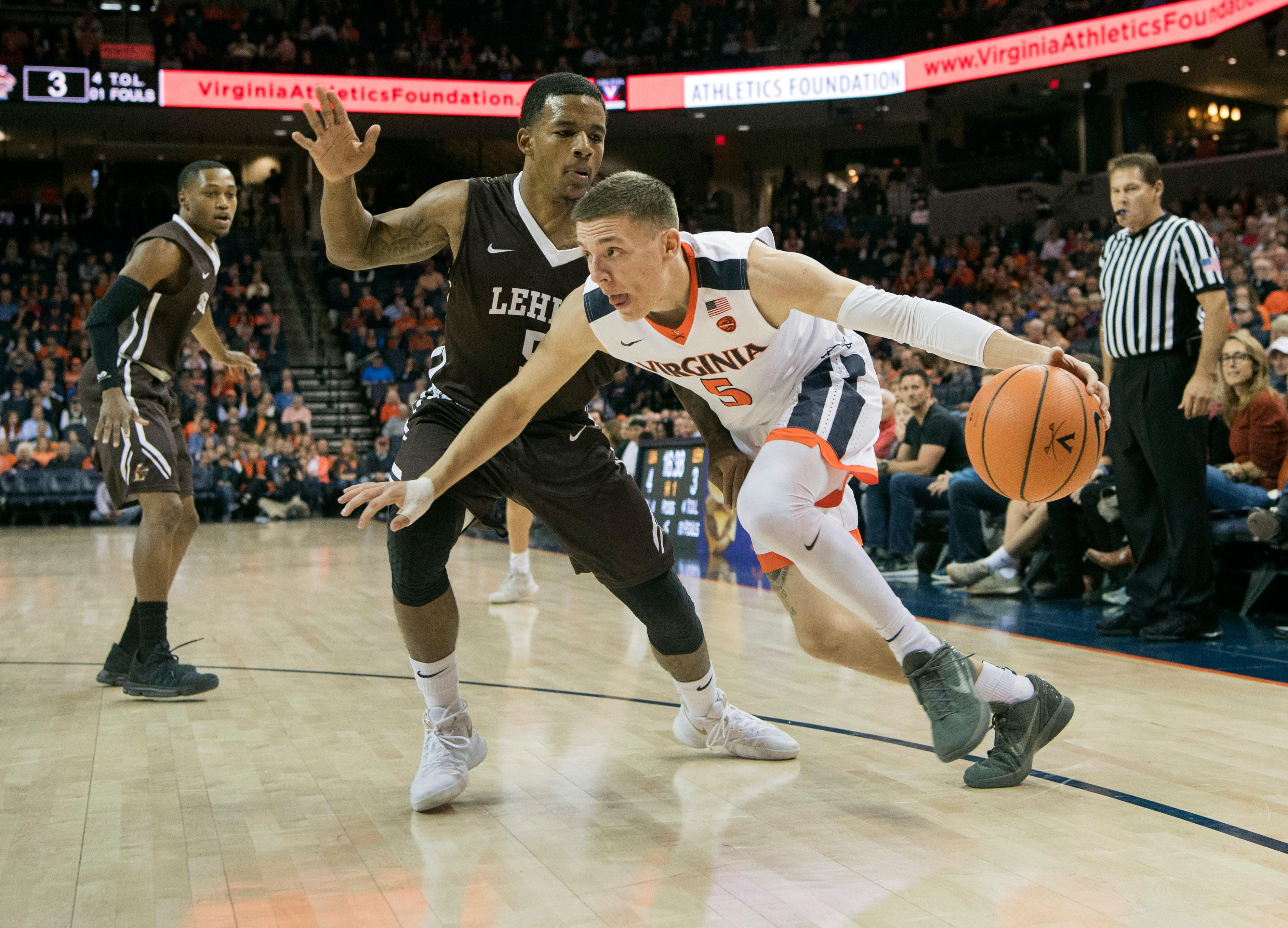 File- This Dec. 2, 2017, file photo shows Virginia's Kyle Guy (5) driving around Lehigh's Lance Tejada (5) during the first half of an NCAA college basketball game in Charlottesville, Va. The sophomore guard is leading the ninth-ranked Cavaliers in scoring entering Saturday's ACC opener against Boston College. (AP Photo/Lee Luther Jr., File)