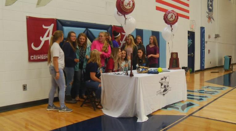 The Enka Sugar Jets surround Kloyee Anderson for a picture as she signs with Alabama (WLOS).jpg