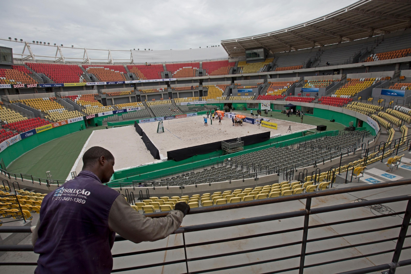 In this Feb. 4, 2017 photo, a worker paints a fence at the Olympic Tennis Center inside Olympic Park in Rio de Janeiro, Brazil. This venue is one of four permanent arenas being run by the federal government, and was used for a one-day beach volleyball tournament, in a city with endless sand and beaches. (AP Photo/Silvia Izquierdo)