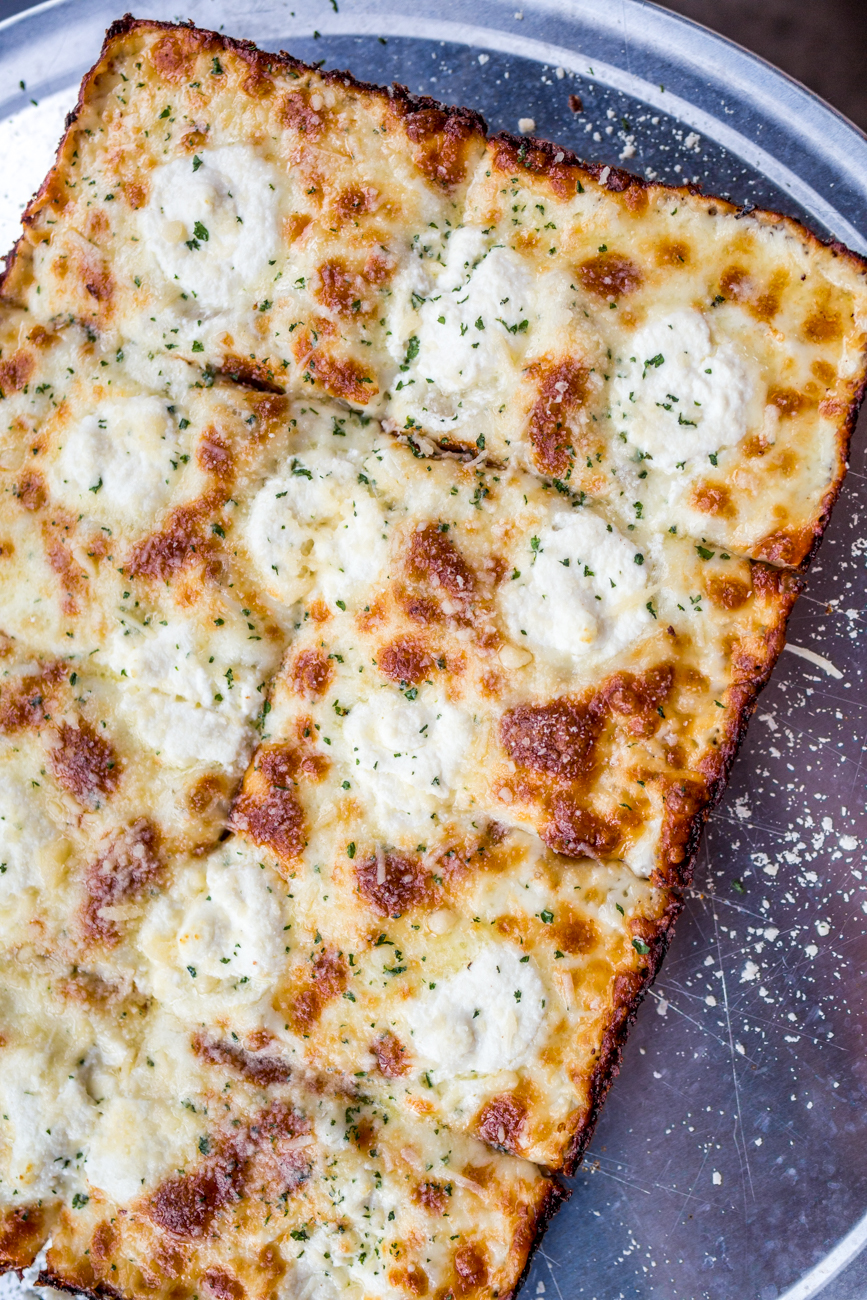 Detroit-style Bianca Pizza: evoo, garlic, parsley, ricotta, parmigiano reggiano, and mozzarella / Image: Catherine Viox // Published: 7.12.19