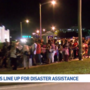 Large crowds gather in early morning darkness for hurricane relief