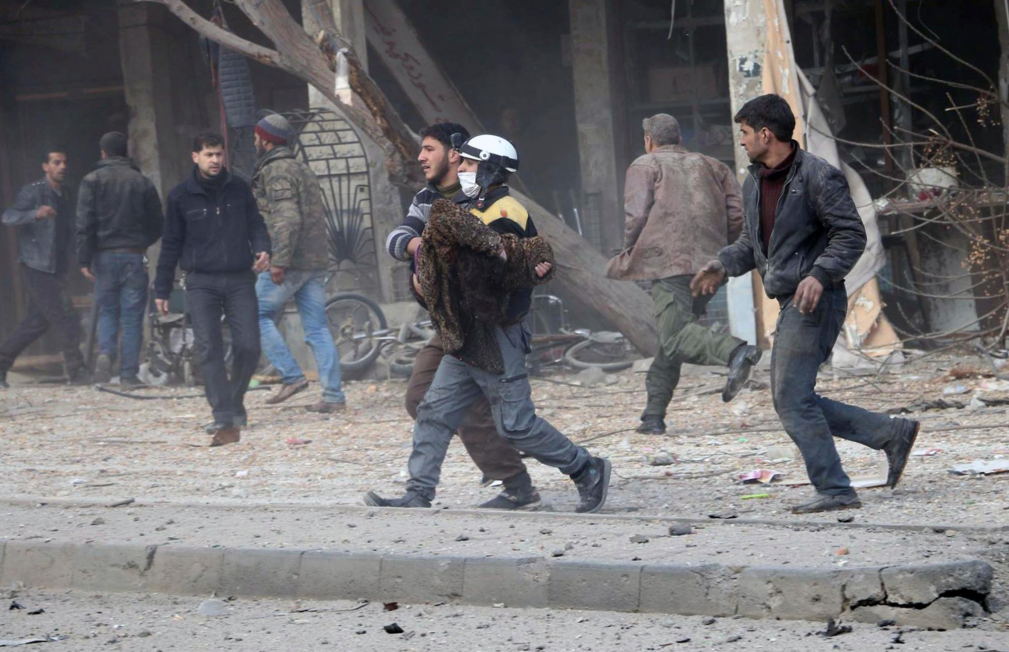 This photo provided by the Syrian Civil Defense White Helmets, which has been authenticated based on its contents and other AP reporting, shows a civil defense worker carrying a victim after airstrikes hit a rebel-held suburb near Damascus, Syria, Thursday, Feb. 8, 2018. Syrian rescue workers and activists say the death toll from ongoing government strikes on the opposition-held region near the capital Damascus has risen to at least 35. (Syrian Civil Defense White Helmets via AP)