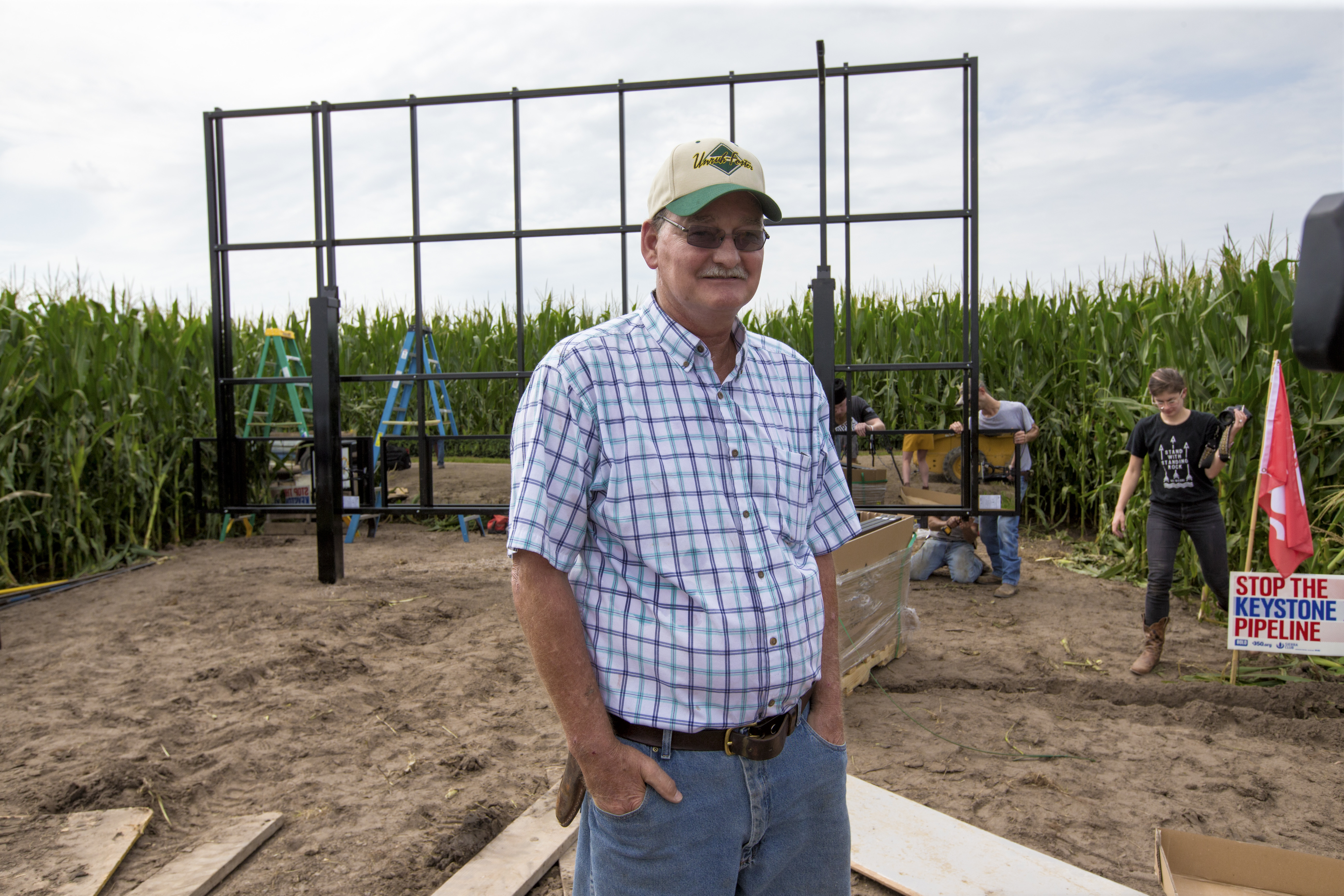 In this July 29, 2017 photo, corn farmer Jim Carlson of Silver Creek, Ne., waits to be interviewed by a television reporter while standing in front of solar panels he is building on his land in the proposed path of the Keystone XL pipeline. Despite new uncertainty over whether TransCanada, the builder of the Keystone XL pipeline will continue the project, longtime opponents in Nebraska aren't letting their guard down and neither are law enforcement officials who may have to react to protests if it wins approval. (AP Photo/Nati Harnik)