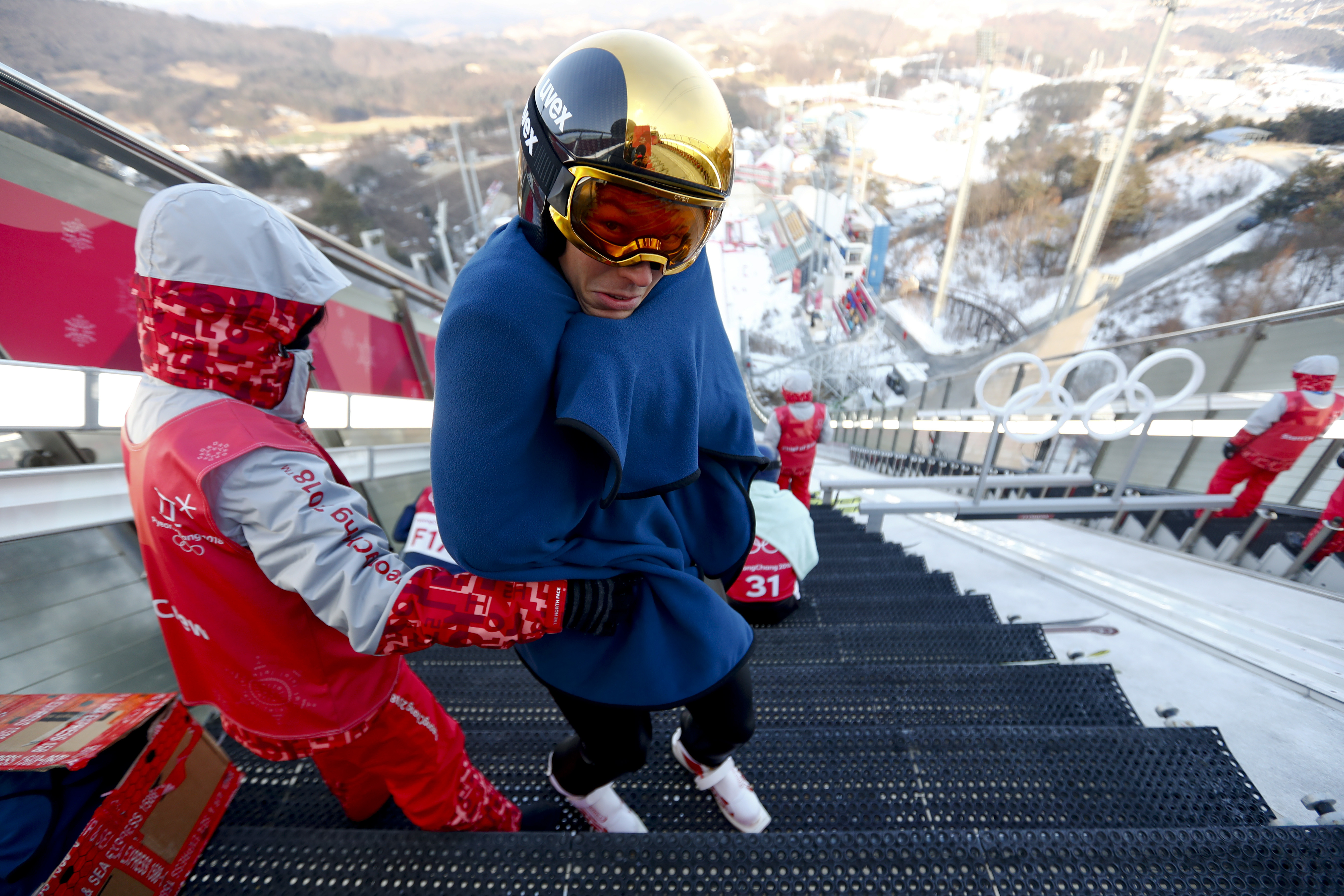Franz-Josef Rehrl, of Austria, wraps himself in a blanket while waiting to jump during training for the men's nordic combined competition at the 2018 Winter Olympics in Pyeongchang, South Korea, Tuesday, Feb. 13, 2018. (AP Photo/Matthias Schrader)