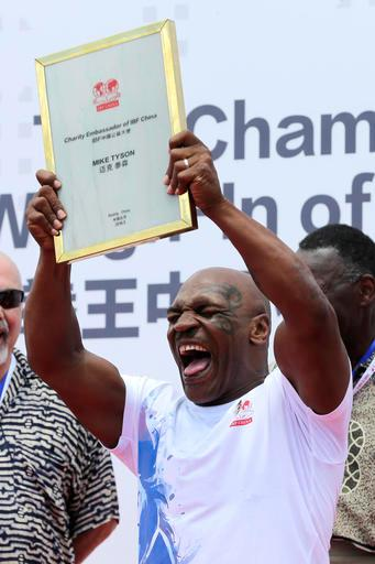Former heavyweight boxing champion Mike Tyson reacts as he is awarded the charity ambassador of IBF China during the weigh-in ceremony of the 2016 IBF World Championship Bout at the Mutianyu section of the Great Wall of China in Beijing, Tuesday, May 24, 2016. Tyson will attend the boxing matches held in the capital city on Wednesday. (AP Photo/Andy Wong)
