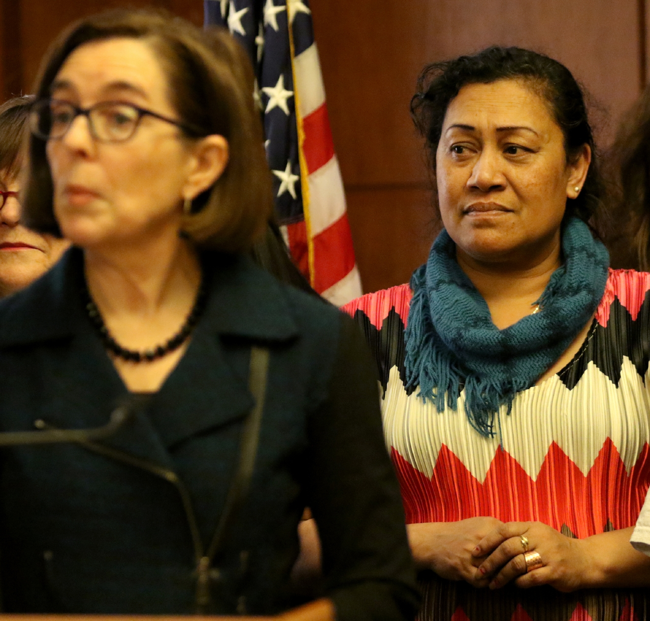 Kasil Kapriel, right, who currently makes $9.25 an hour, stands behind Gov. Kate Brown before she signs Senate Bill 1532, increasing Oregon's minimum wage according to a tiered system, at the State Capitol in Salem on Wednesday, March 2, 2016. PortlandÂ?s minimum will rise to $14.75 by 2022, suburban areas to $13.50 and rural areas to $12.50. The tiered approach is based on economic factors.  (Anna Reed/Statesman-Journal via AP) MANDATORY CREDIT