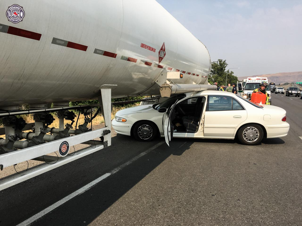 Car becomes lodged under semi, both occupants uninjured